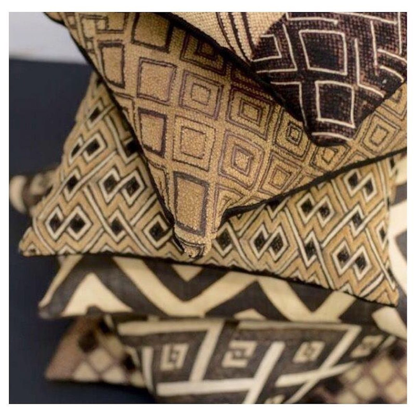 A stack of pillows in African designs in a kuba / raffia material