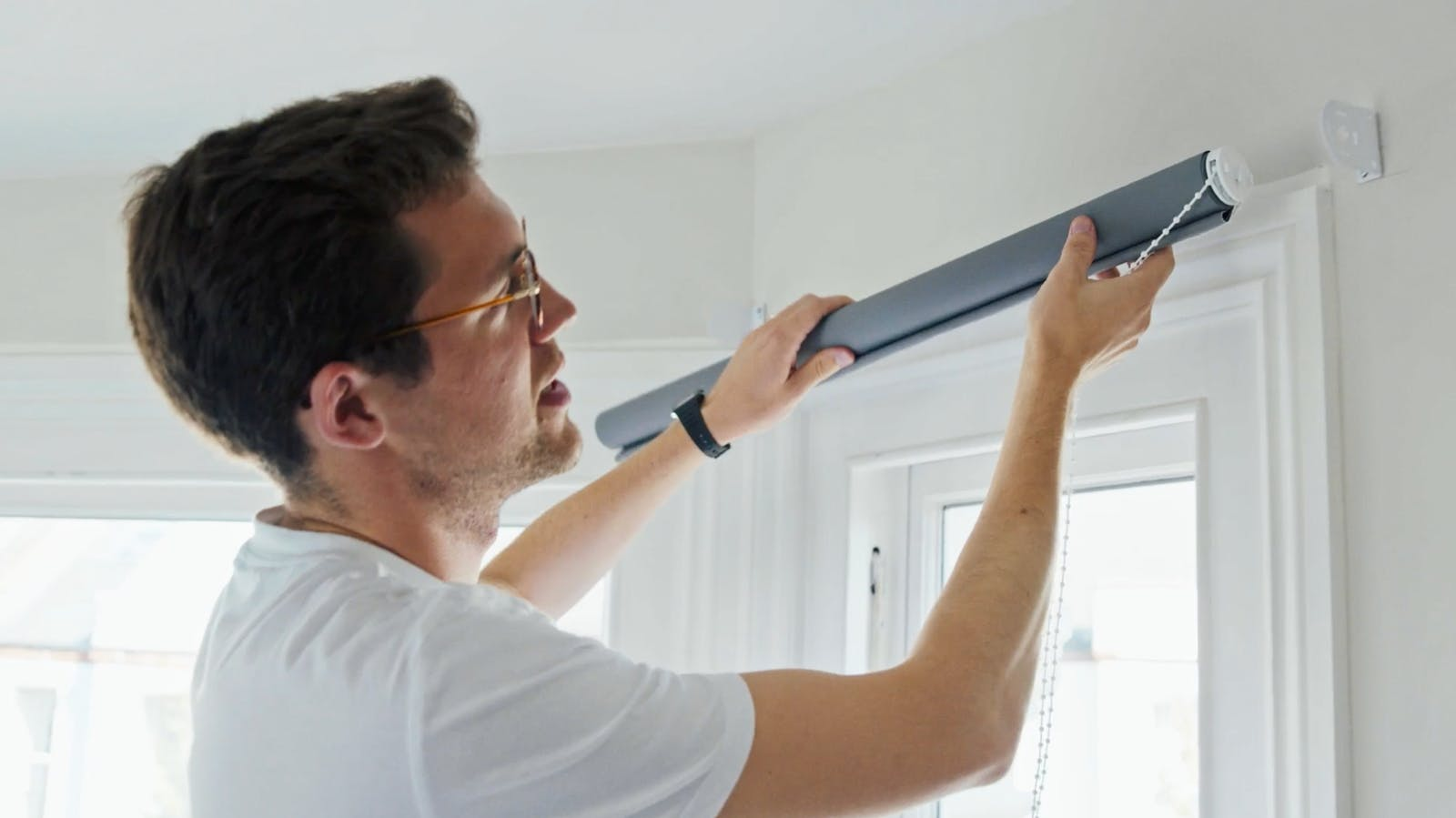 Man holding grey roller blinds in hand