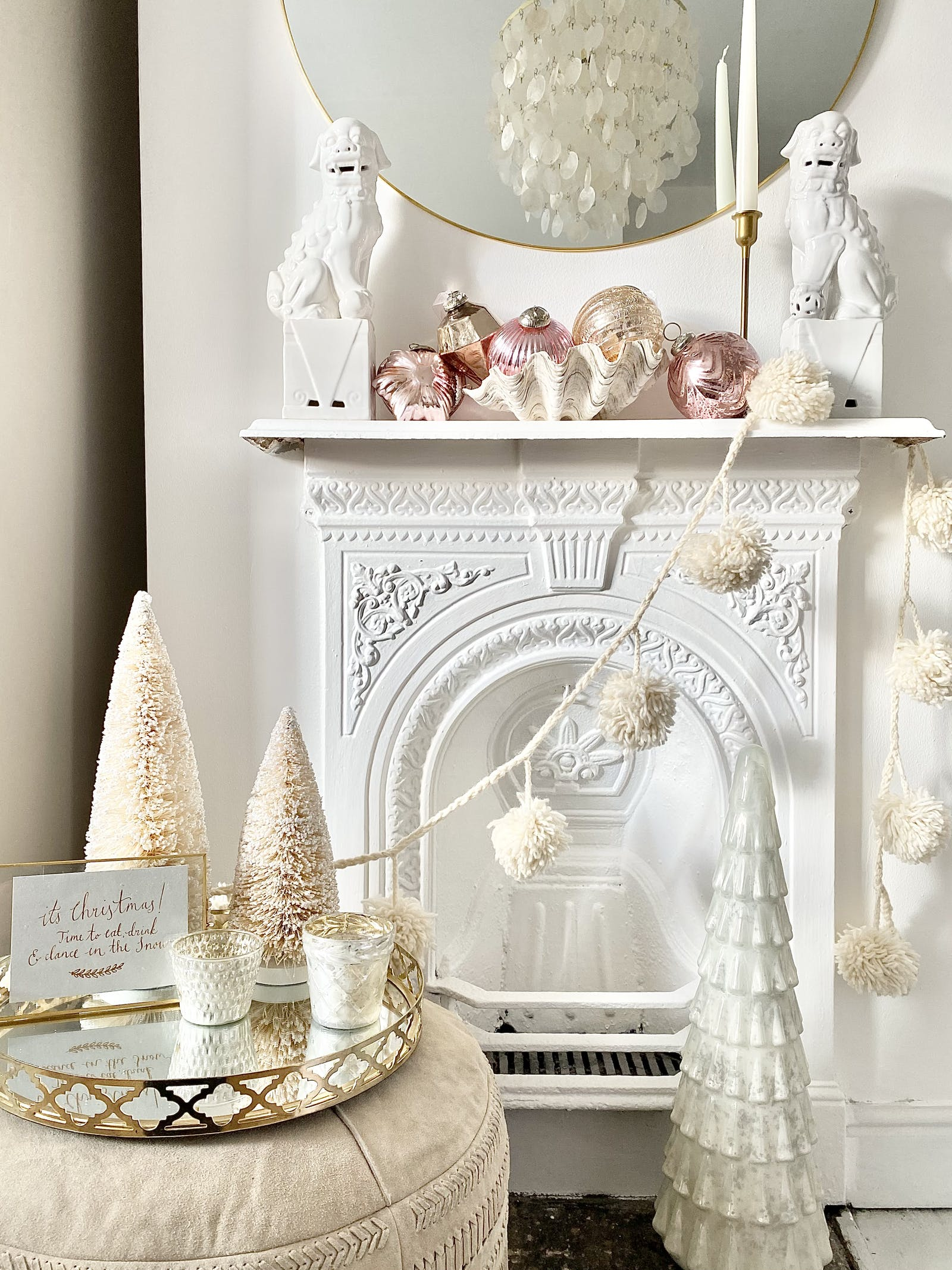 White fireplace with various Christmas decorations and a white garland