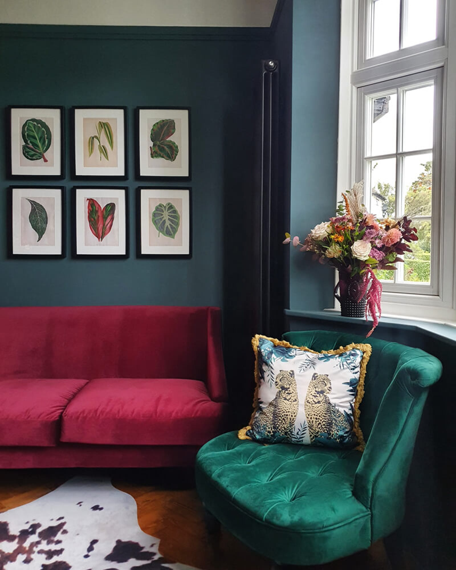 Living room with velvet sofas and dark green walls