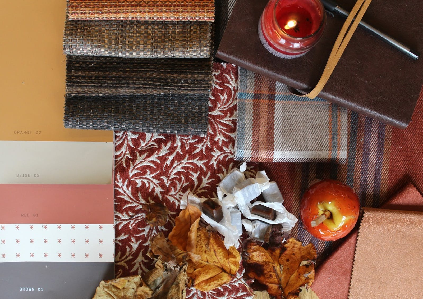 Autumnal setting with leaves, toffee apples and Lick Orange, Red and Brown paint samples