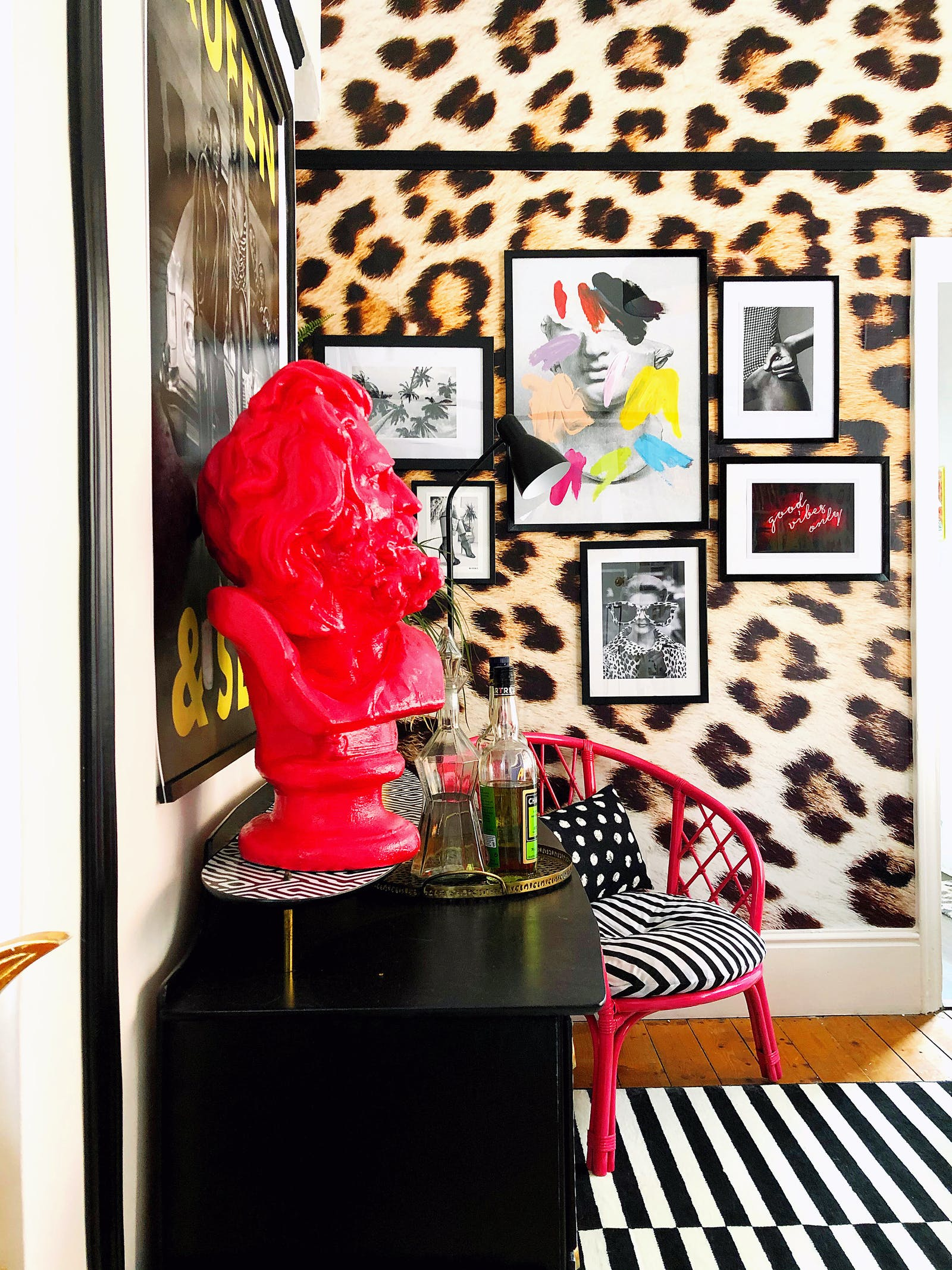 A pink head sculpture in a living room with cheetah wallpaper
