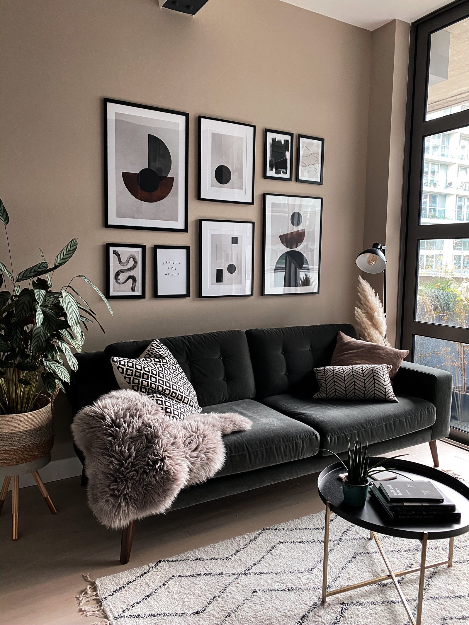 Living room with a dark sofa in front of a beige gallery wall