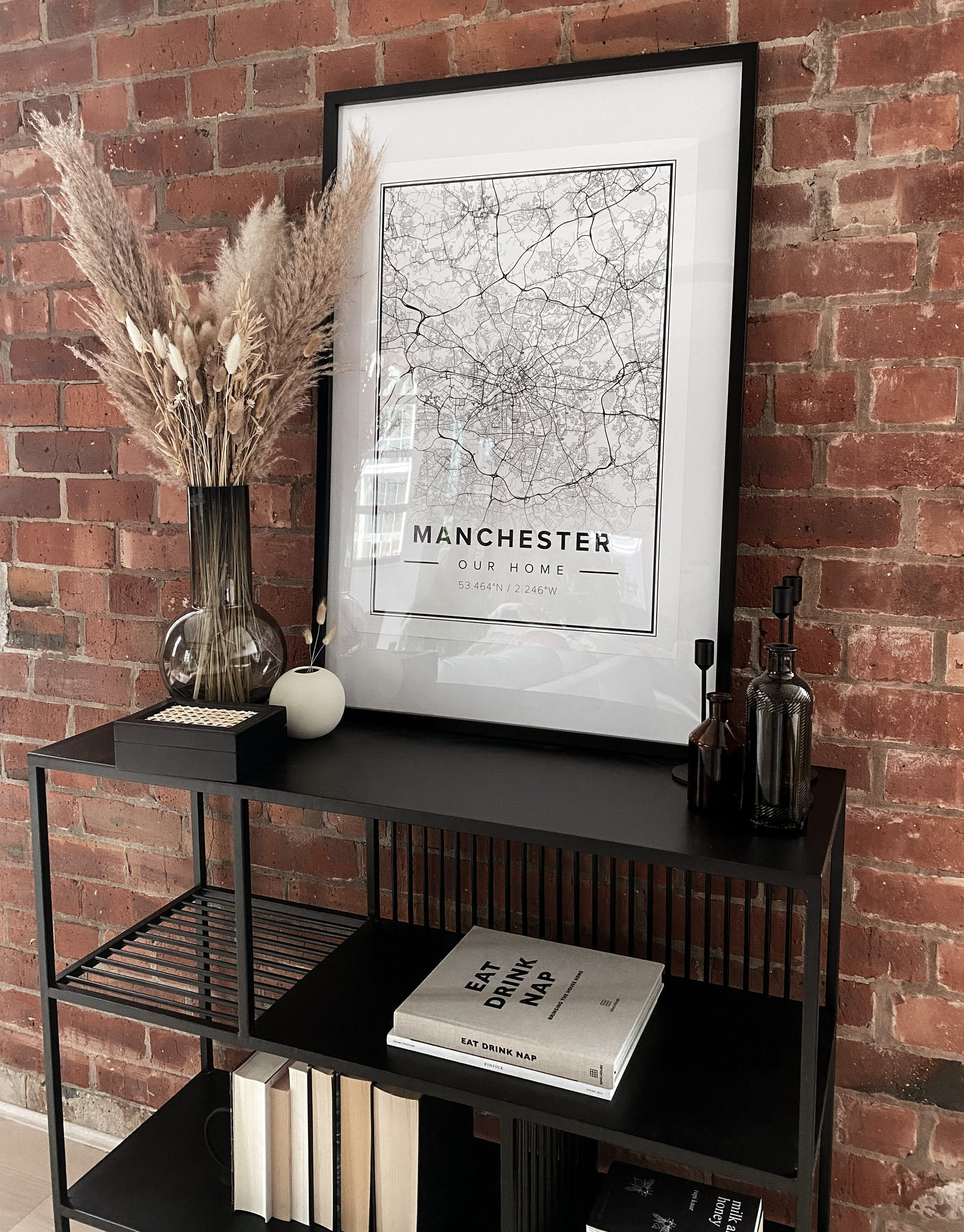 Exposed brick wall with a Manchester map poster and books