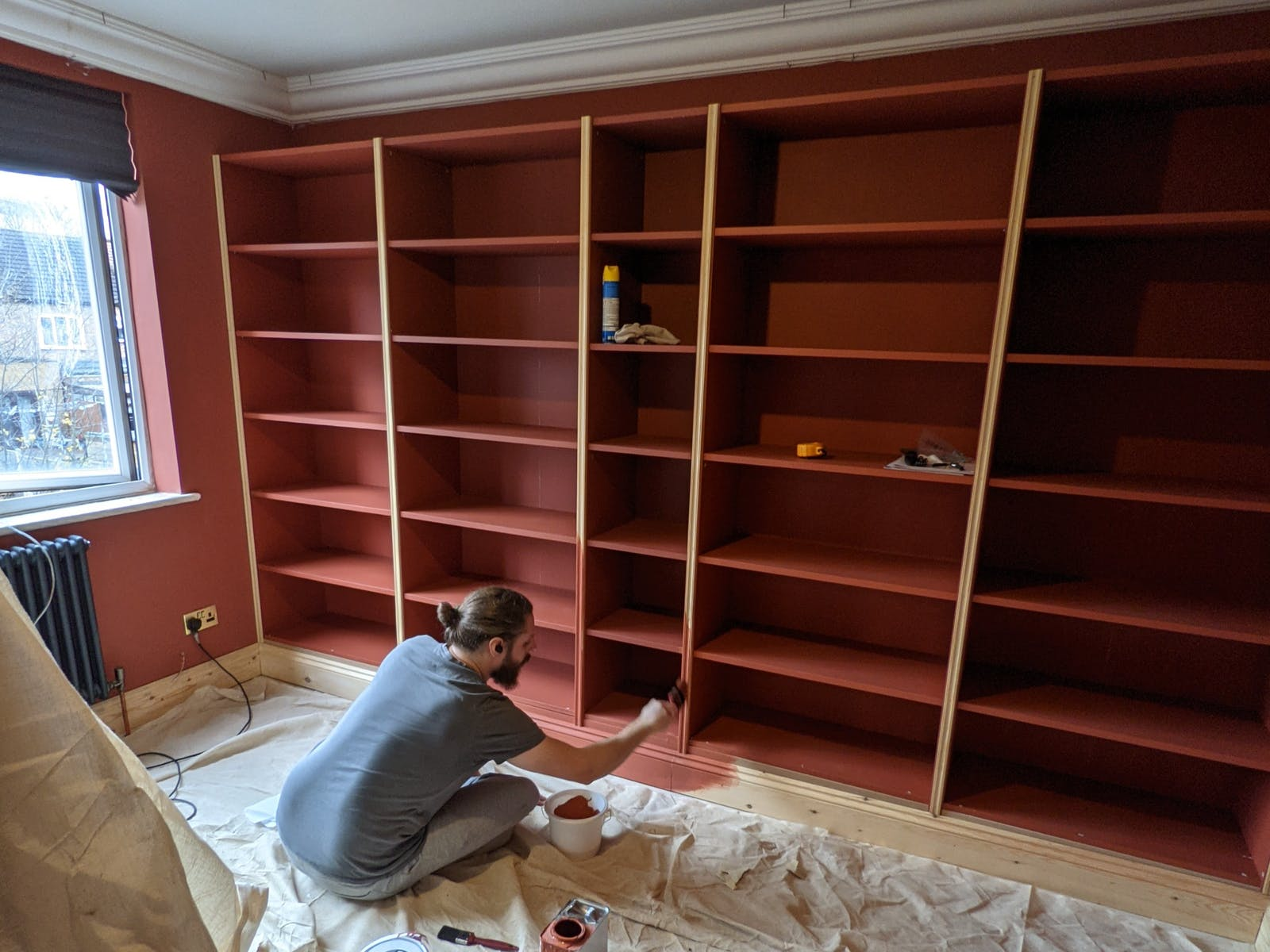 Man doing some DIY on an Ikea Billy Bookcase painted in Lick Red 01
