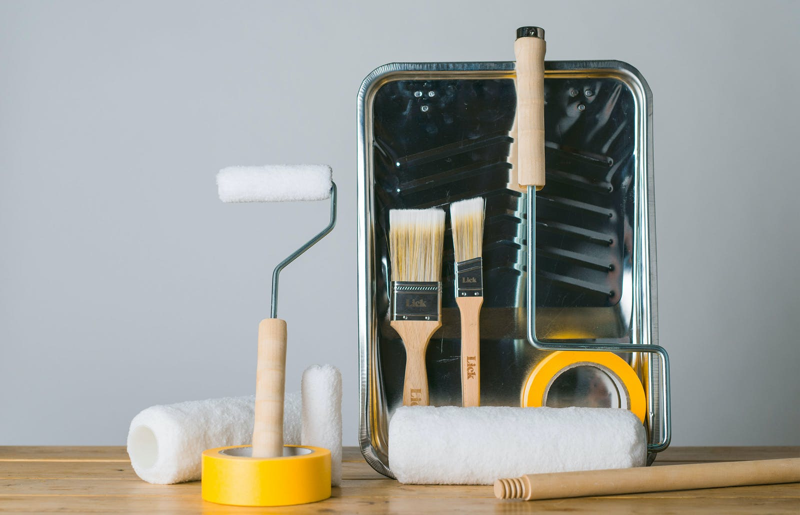 A collection of Lick painting and decorating tools including yellow tape, brushes, rollers and a tray.