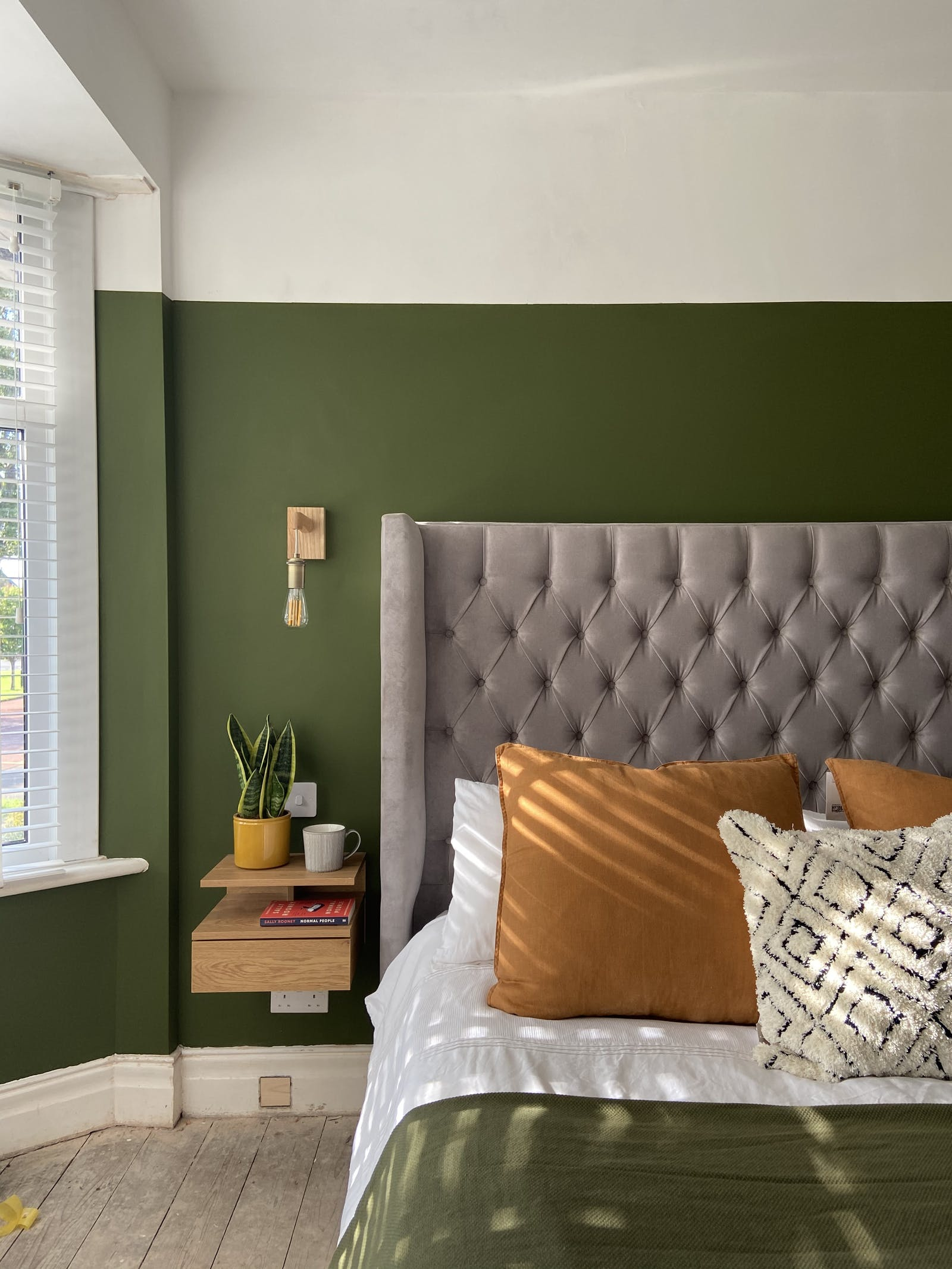 Colourful bedroom with large velour headboard against a Lick Green 05 wall