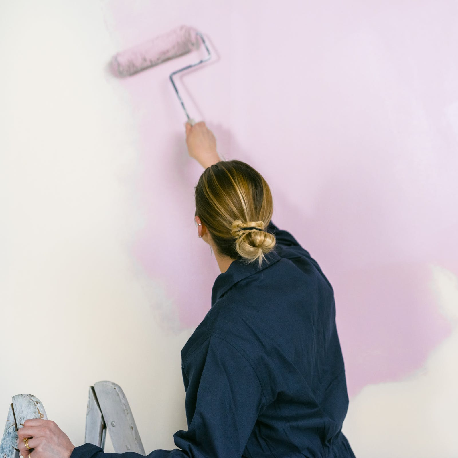 Blonde woman painting a pink paint on wall with a roller brush