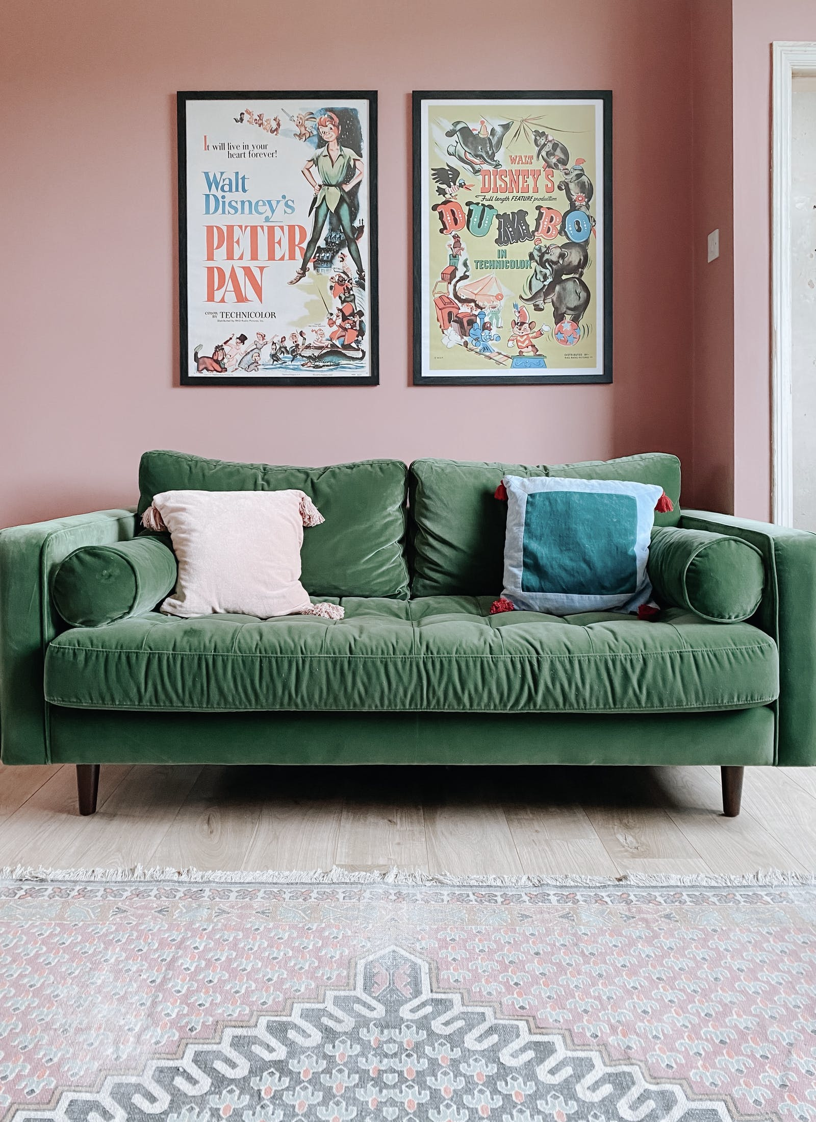 Green velvet three-seater sofa on wooden floor against a bubblegum pink wall with Disney posters