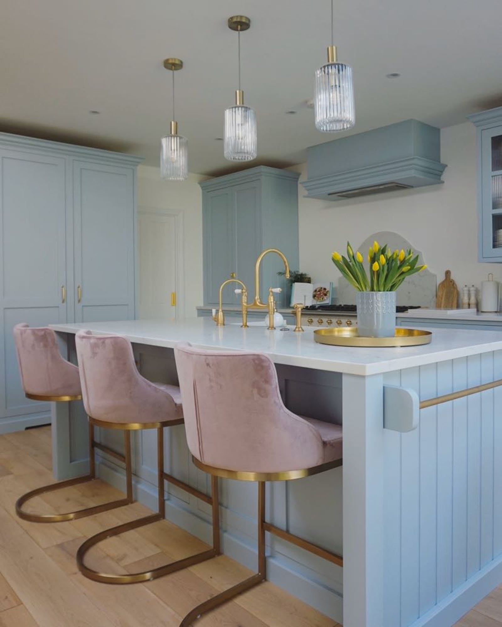 Light blue kitchen with pink velvety chairs