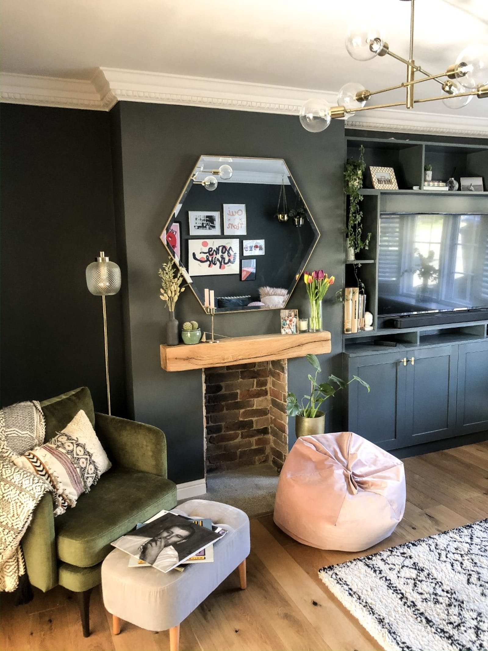 Living room painted in dark teal with armchair and soft furnishings