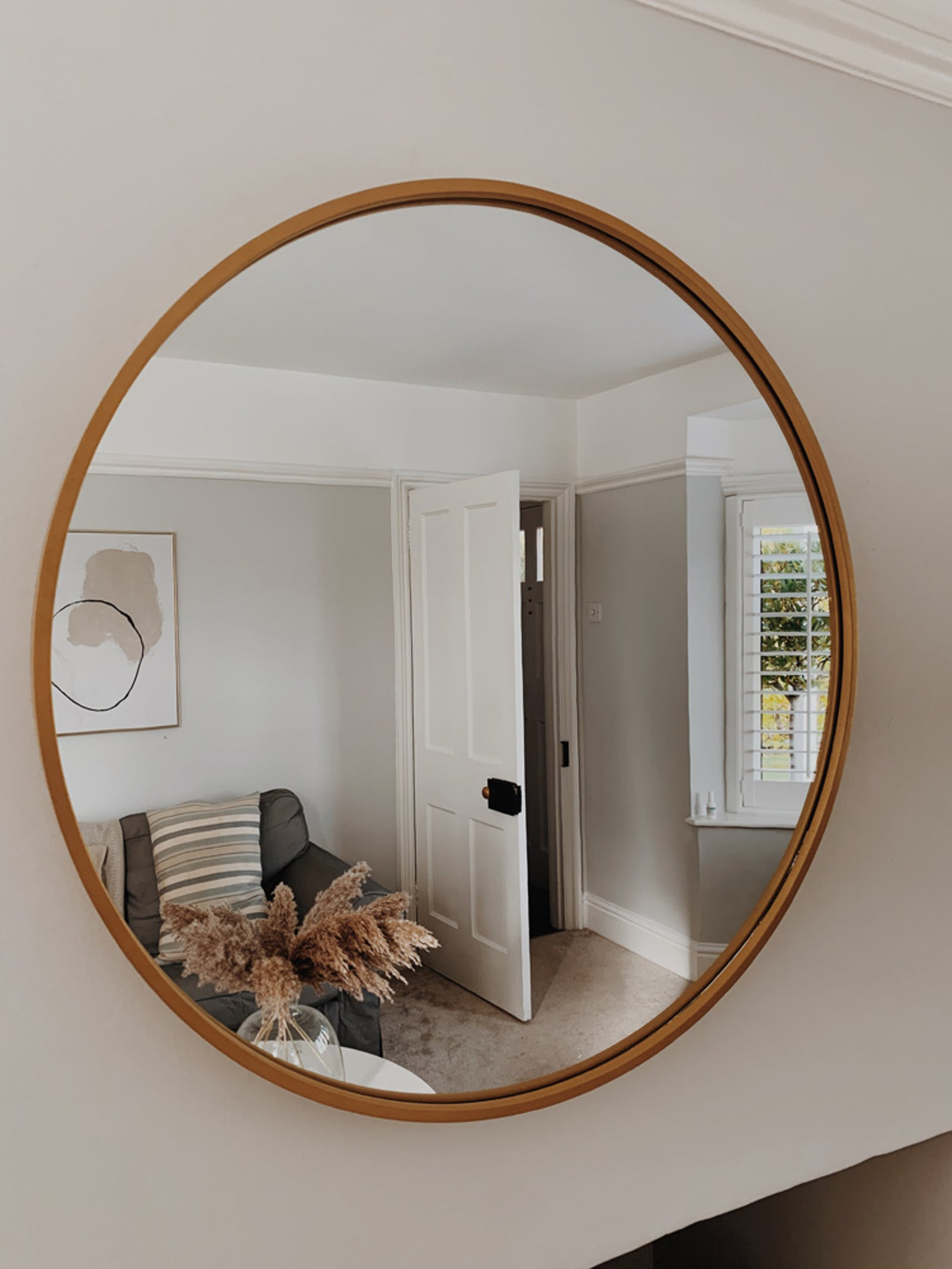Living room painted in Lick Grey 01, seen in the reflection of a large circle mirror