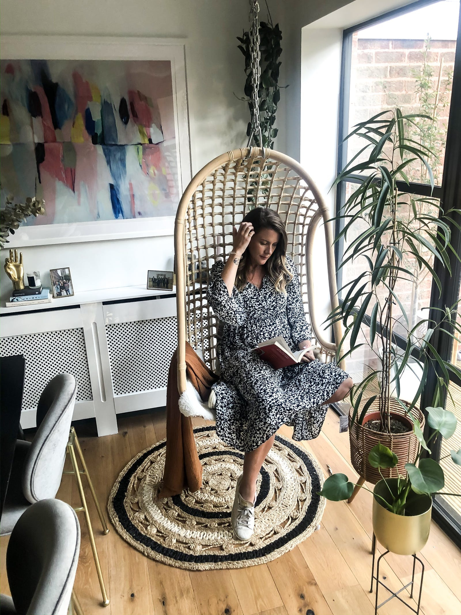 A woman sitting in a rattan chair swing and reading a book, with an abstract colourful painting behind her