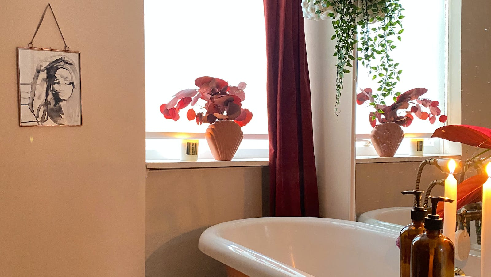 Image of cosy bathtub scene with lit candles, flowers and hanging plants.