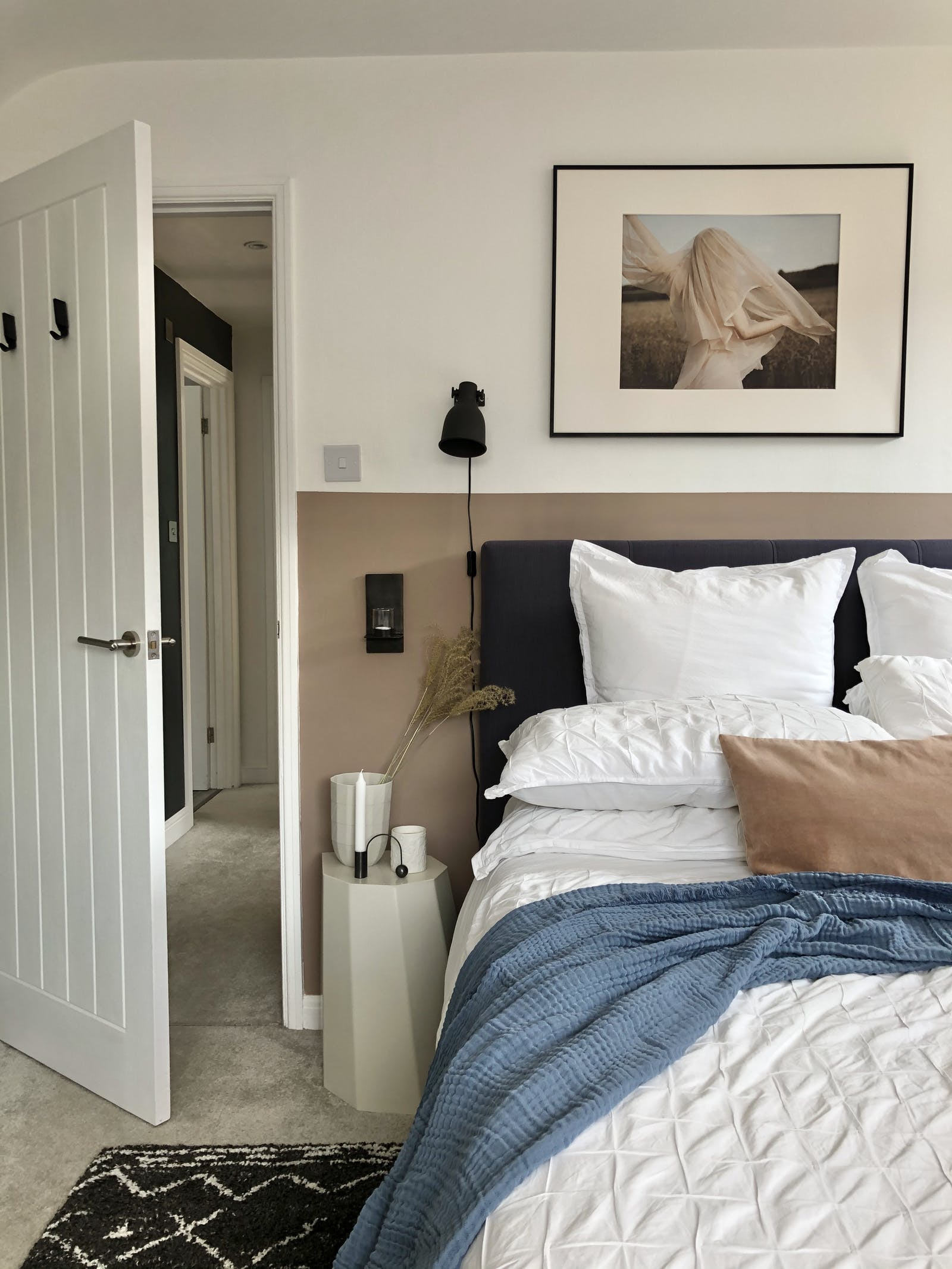 Master bedroom with neutral and white walls and white bedding on bed
