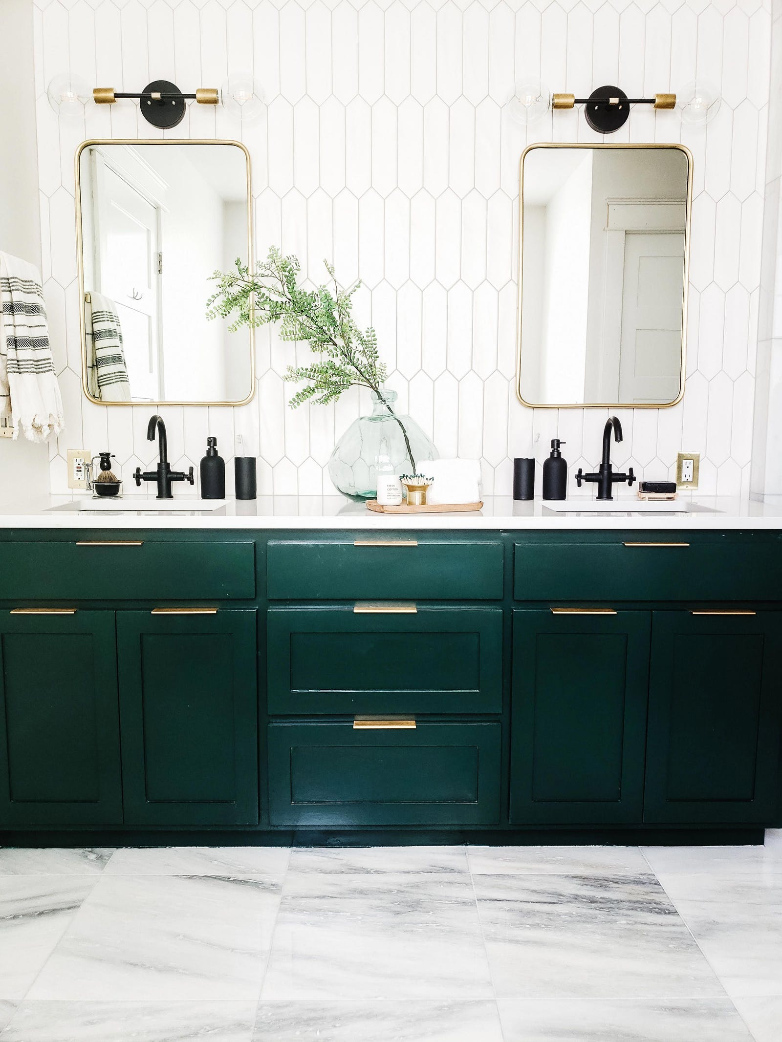Bright bathroom with emerald green cabinets and tile walls