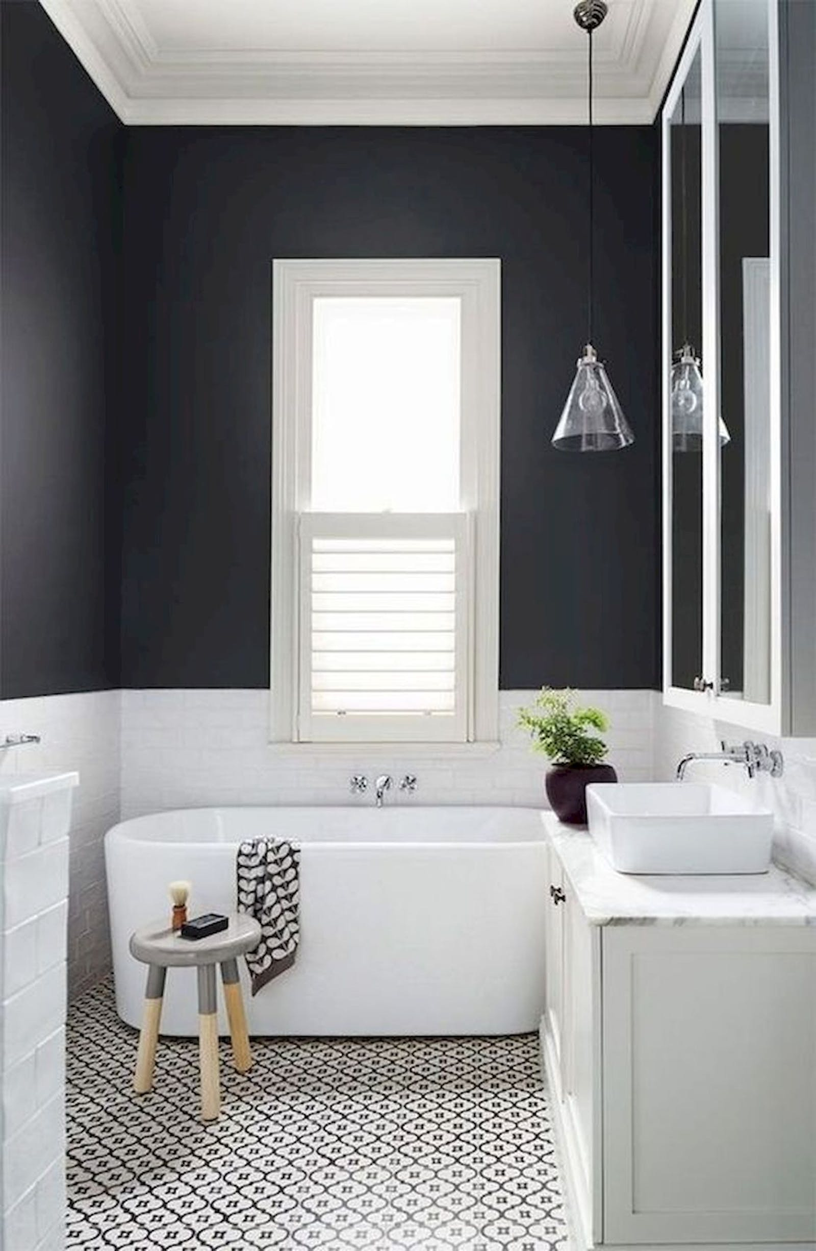 Black bathroom with a bathtub and patterned tiles