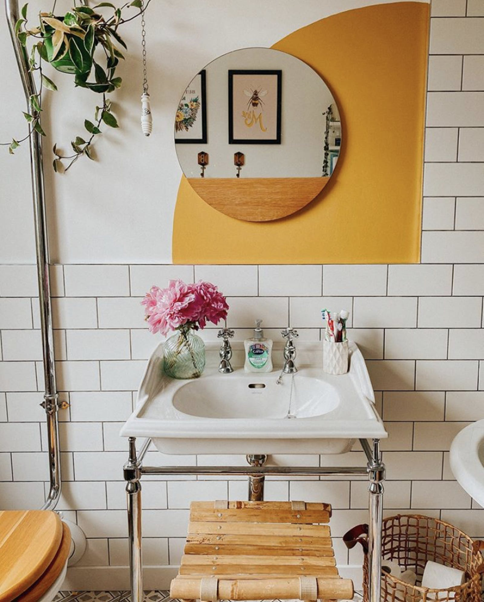 Bathroom wall with orange decal behind a round mirror