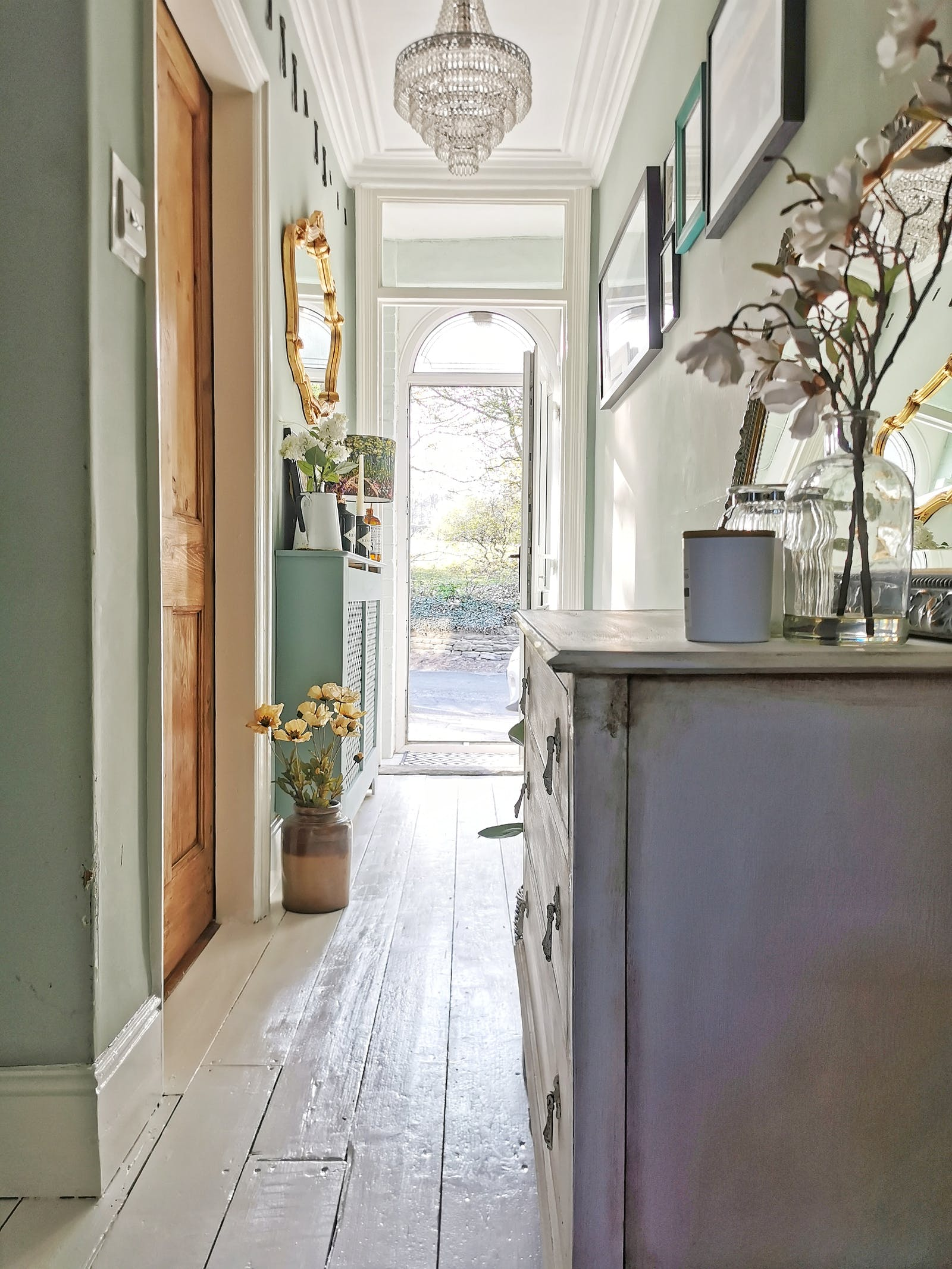 A bright hallway painted in a light green colour with some vintage wooden furniture and floorboards painted in white