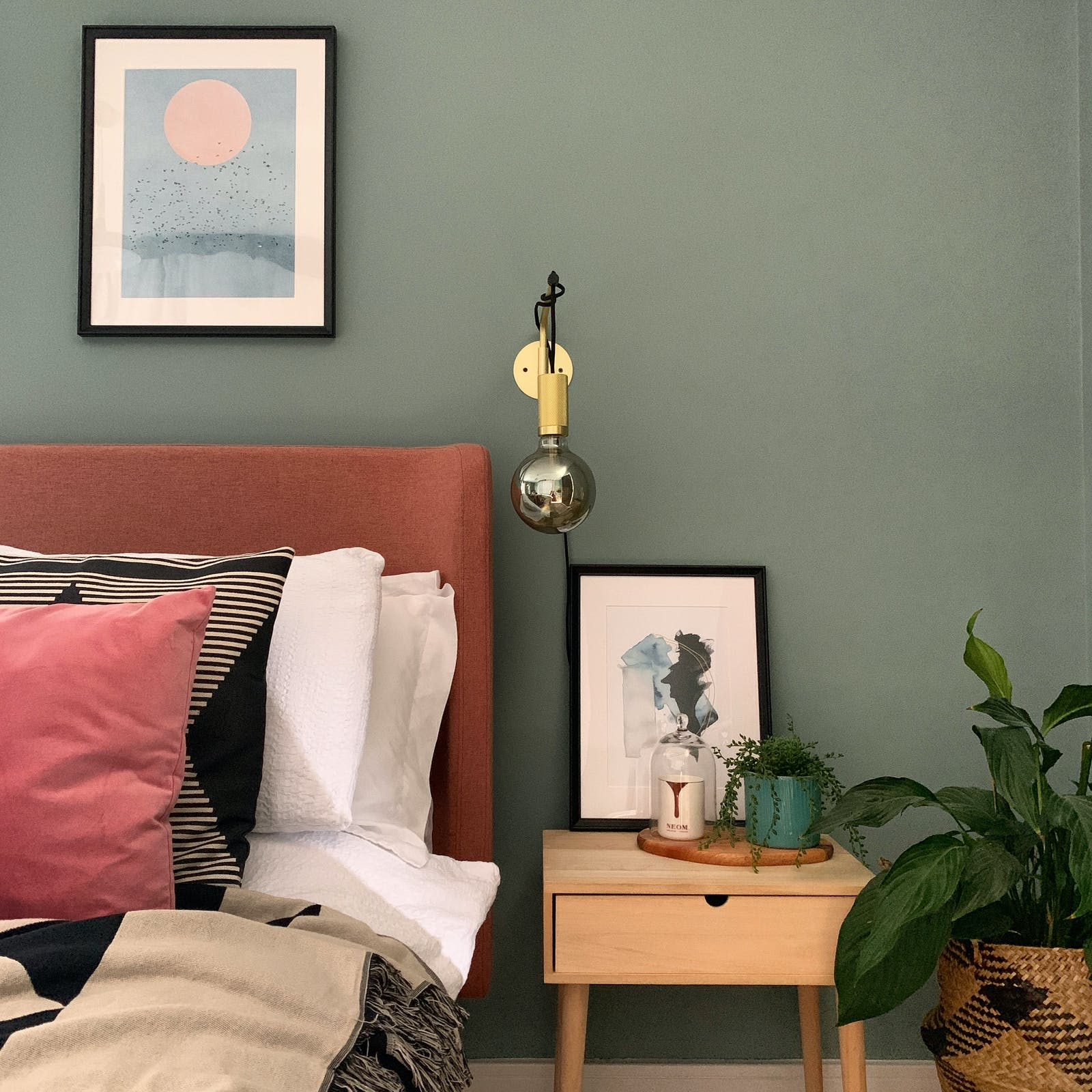 Close up image of bedroom with plants, artwork and pink, black and beige pillows