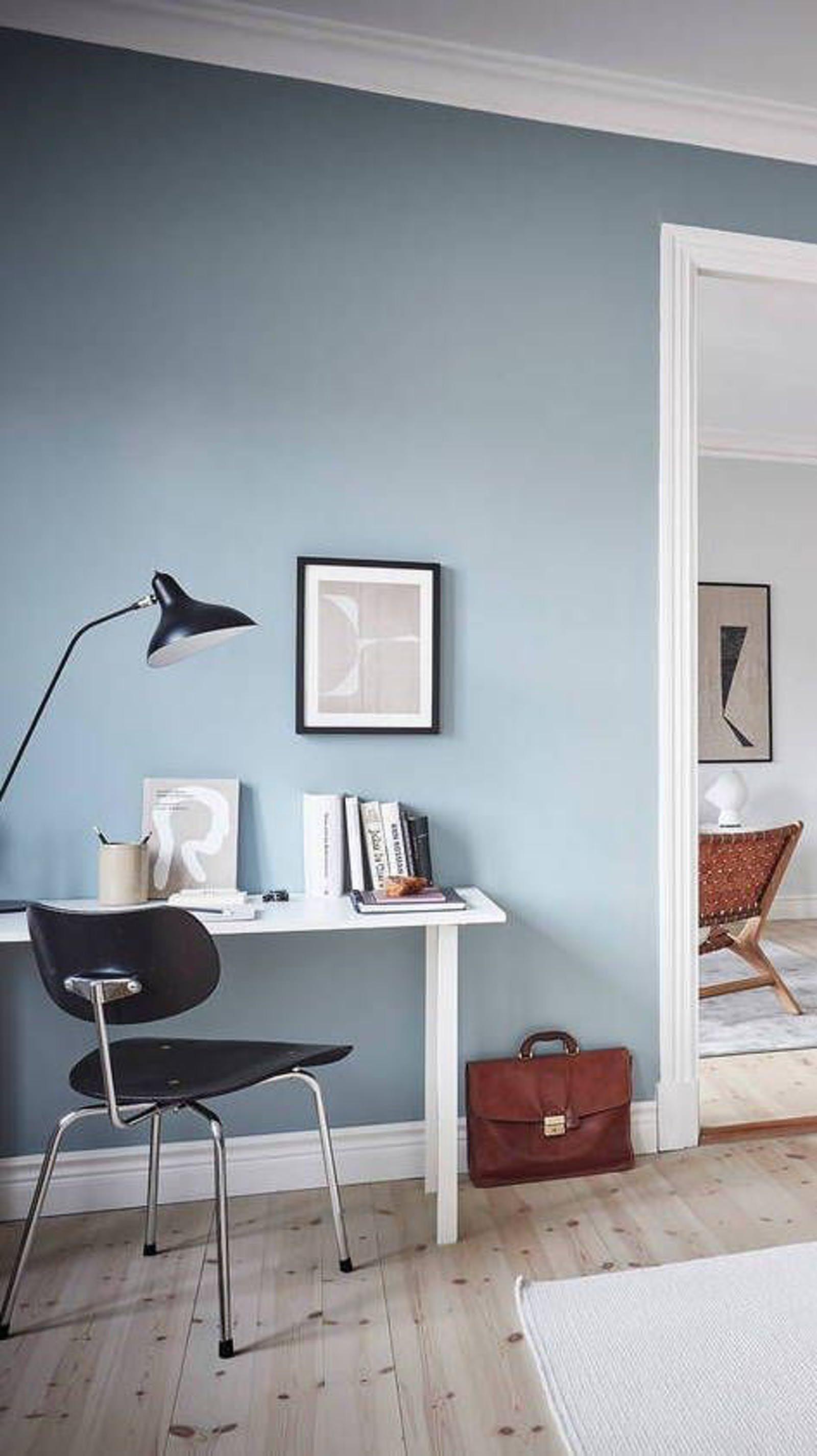 Home office area with minimalistic design and a wall painted in bright blue