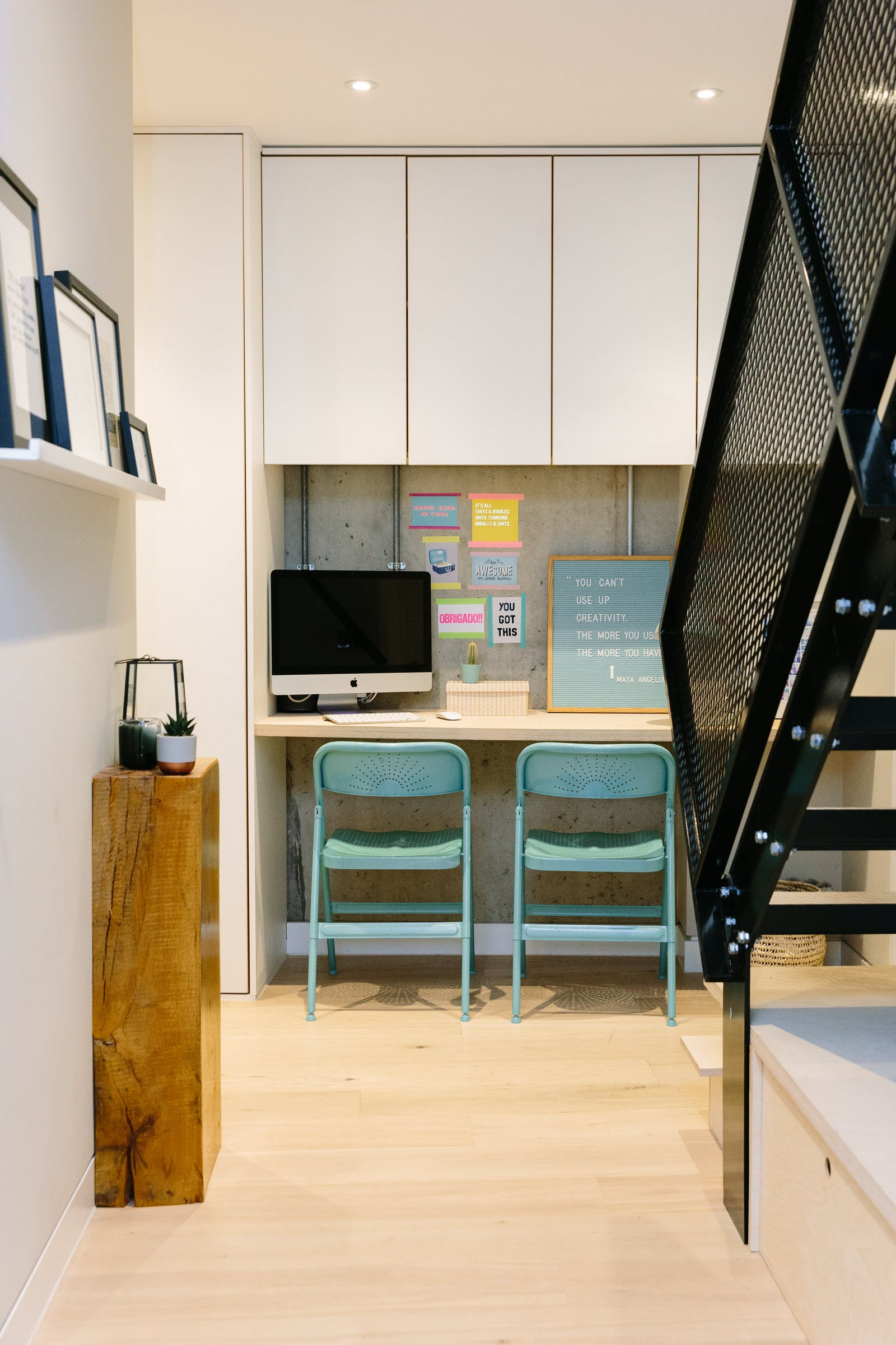 Minimal home office at the bottom of some stairs, with blue chairs and white cupboards