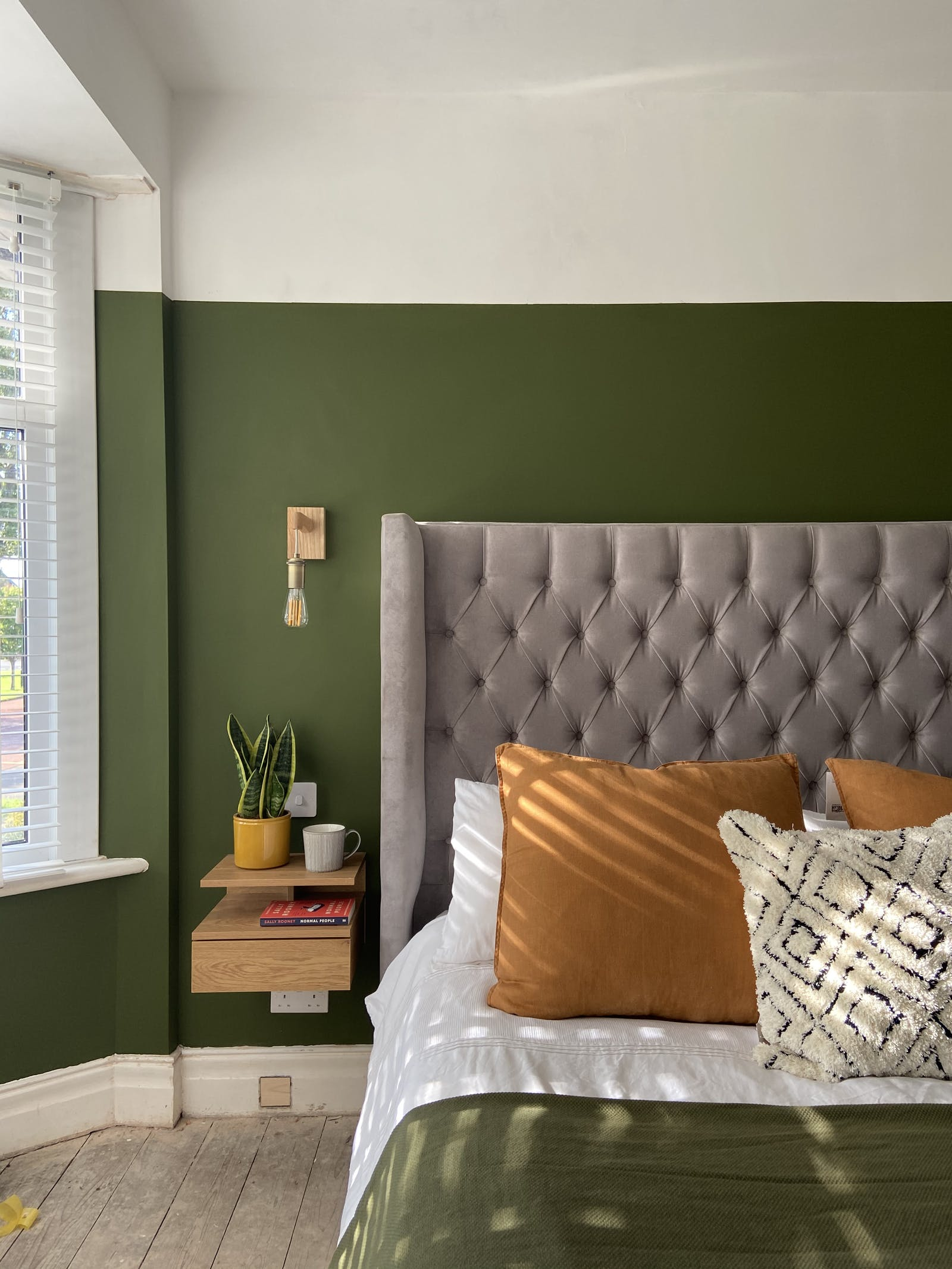 Bedroom with large grey headboard, orange cushions and Green 05 painted walls