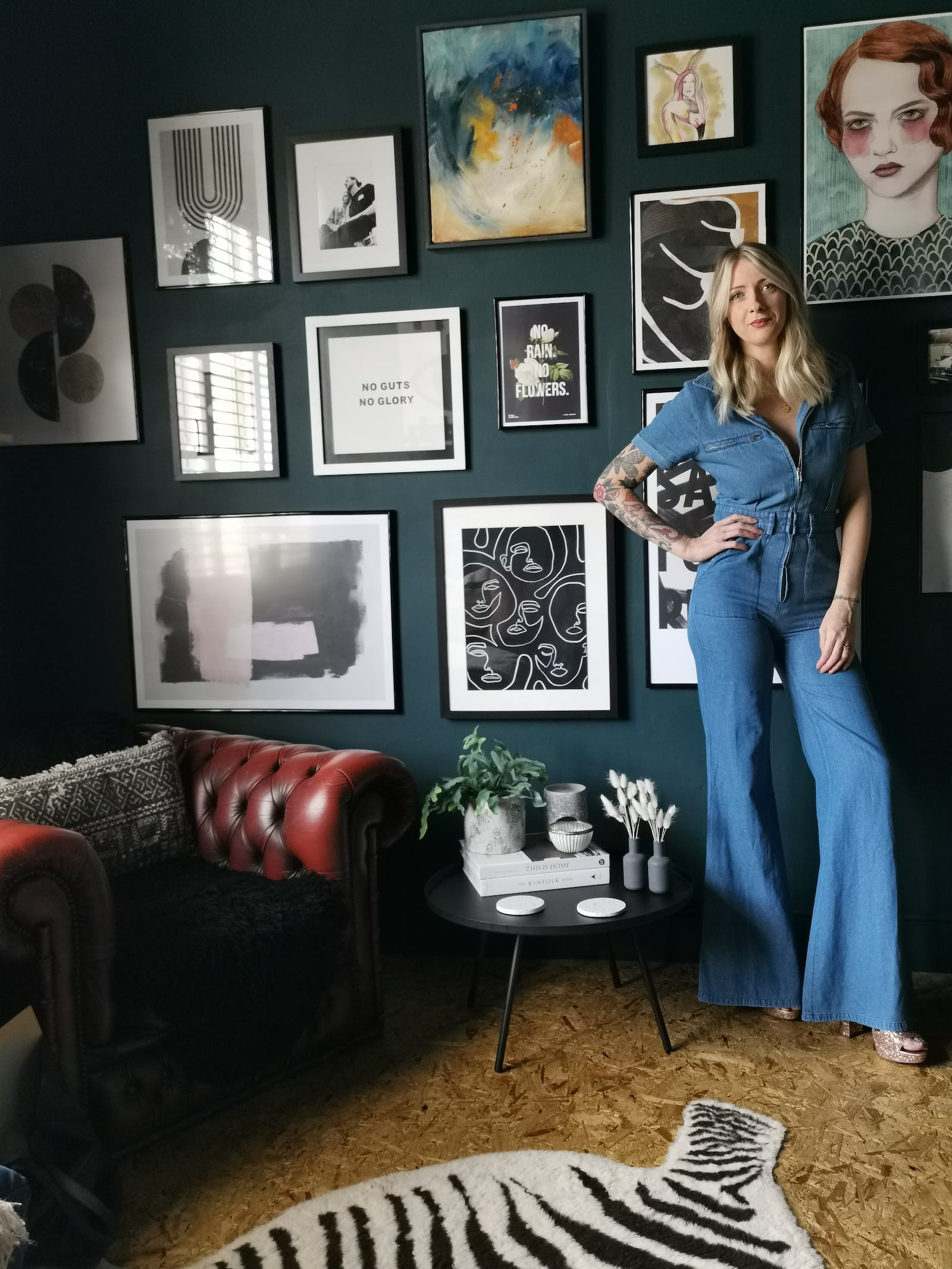 Blonde woman in a denim jumpsuit posing in front of a gallery wall painted in dark teal