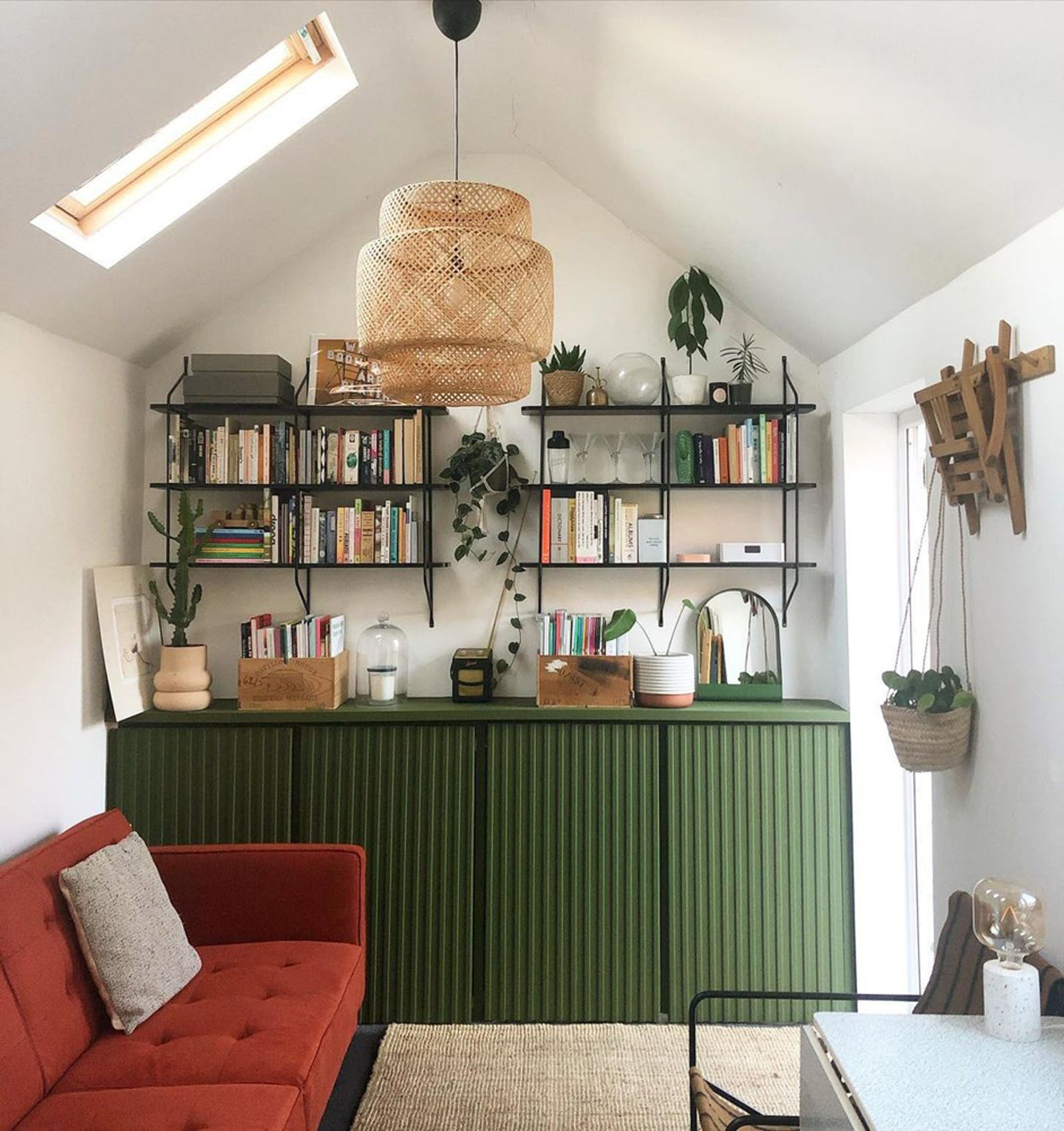 Open shelving on top of green cupboards and hanging plants