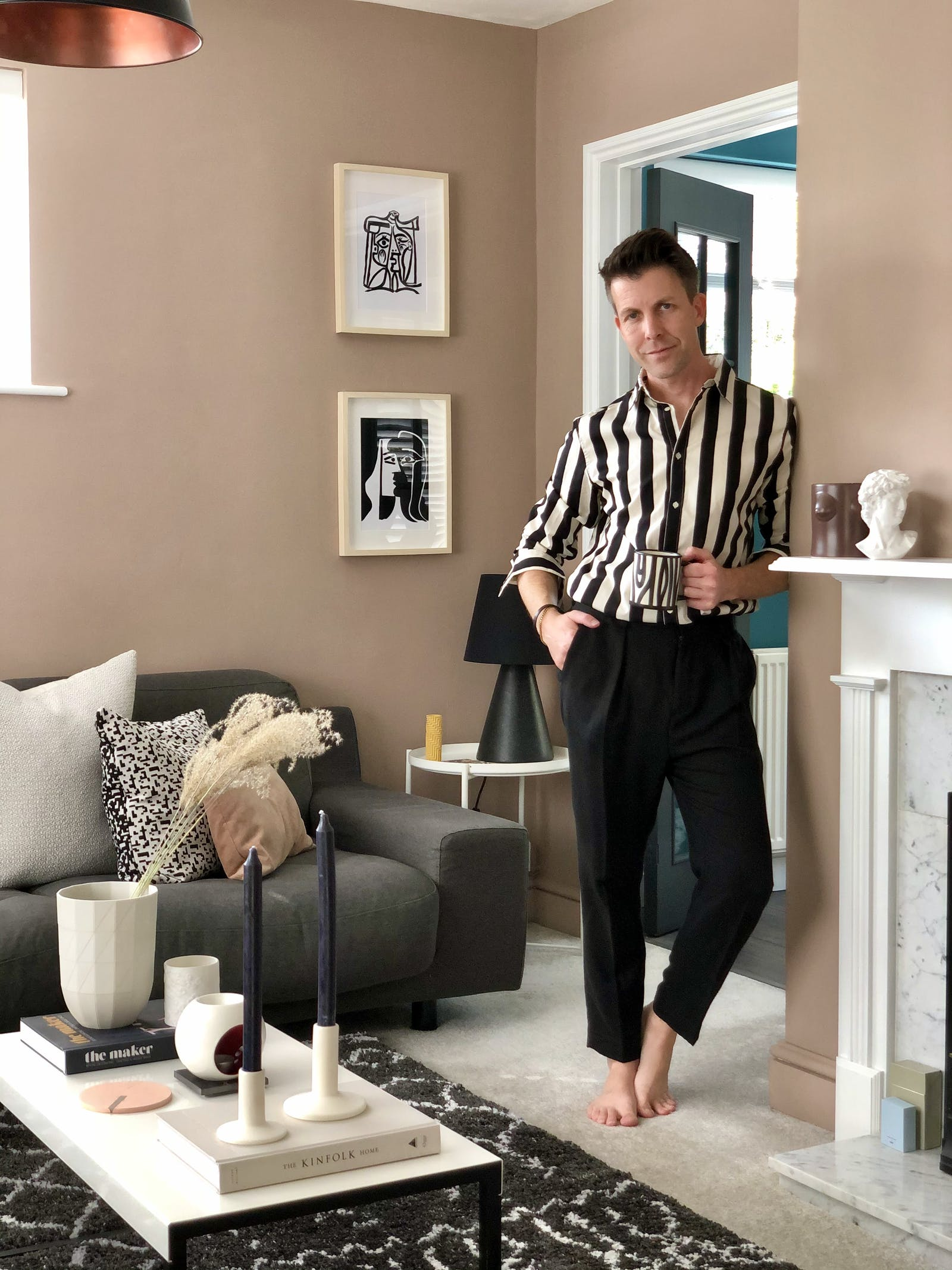 Man standing in neutral beige painted living room with grey velvet sofa and black and white soft furnishings
