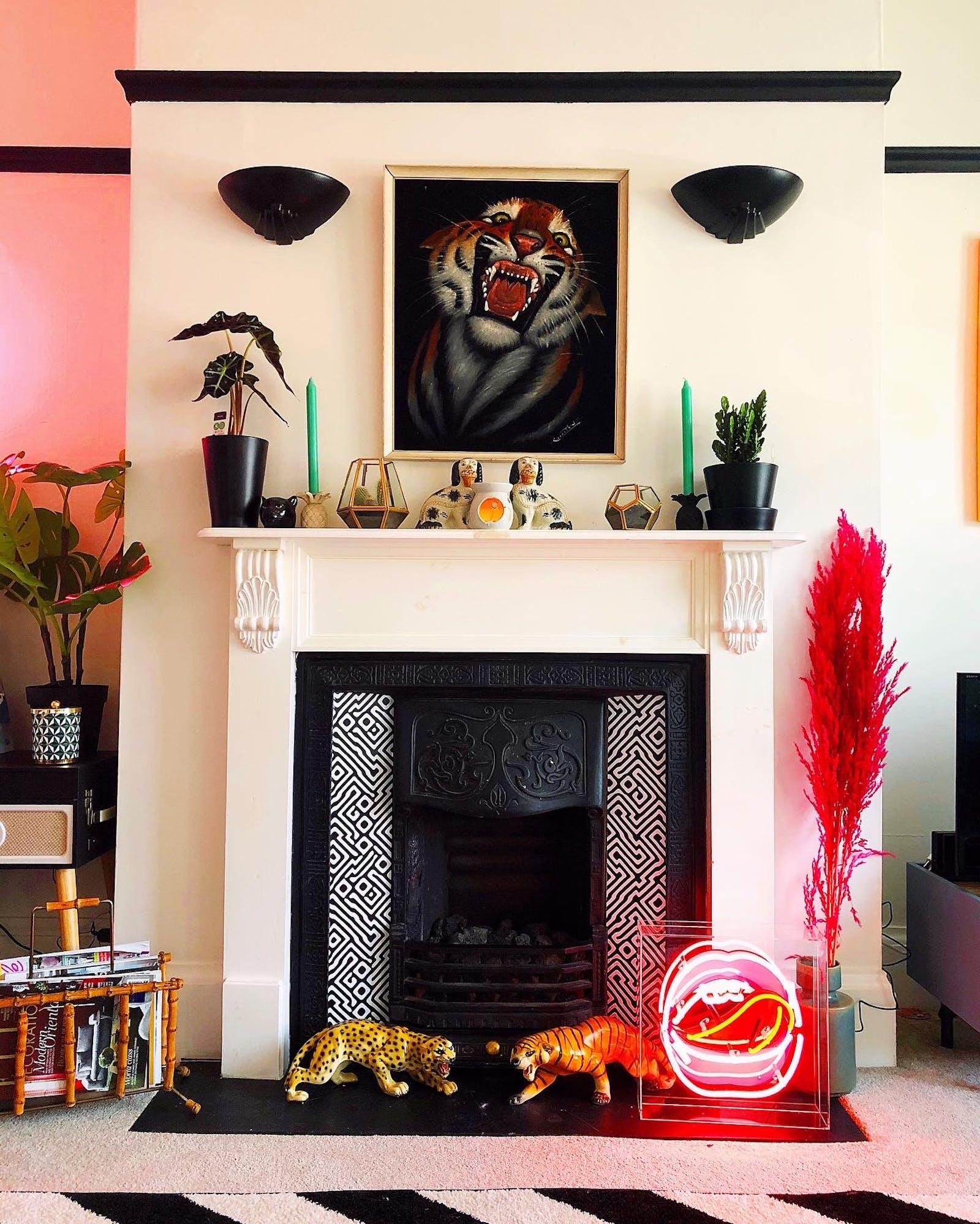 RHOI tiger painting, neon lips and vibrant accessories accompany a geometrically painted black and white fireplace