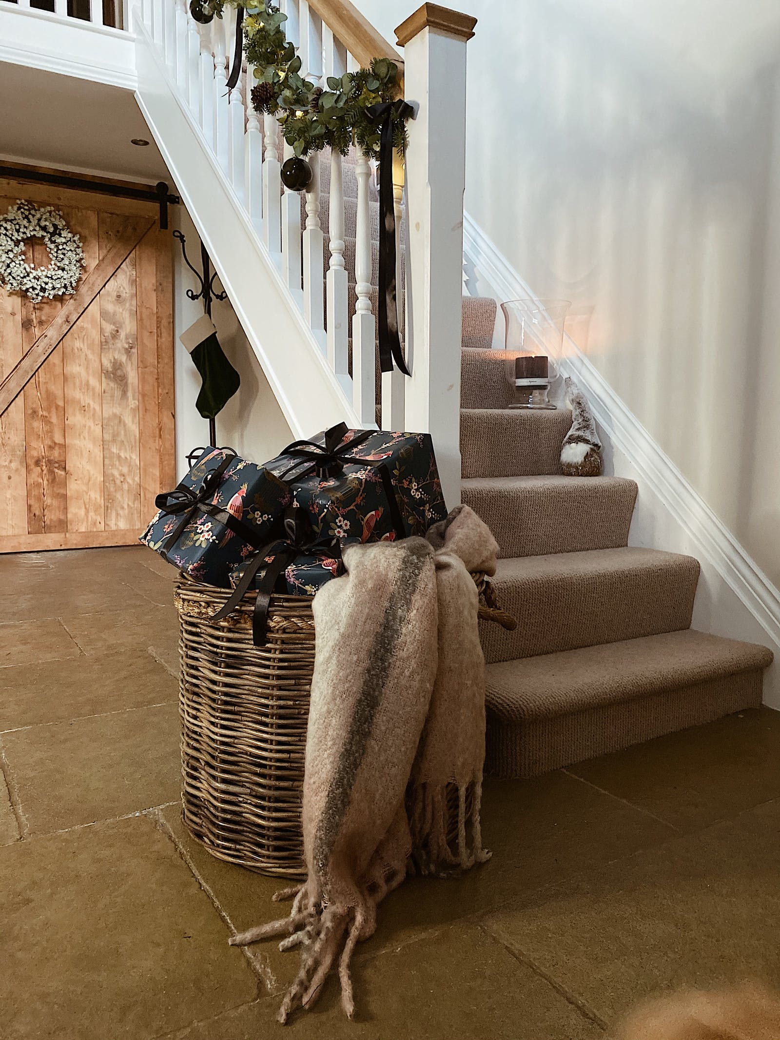 Hallway with big woven basket with gifts and fresh foliage on the stairwell