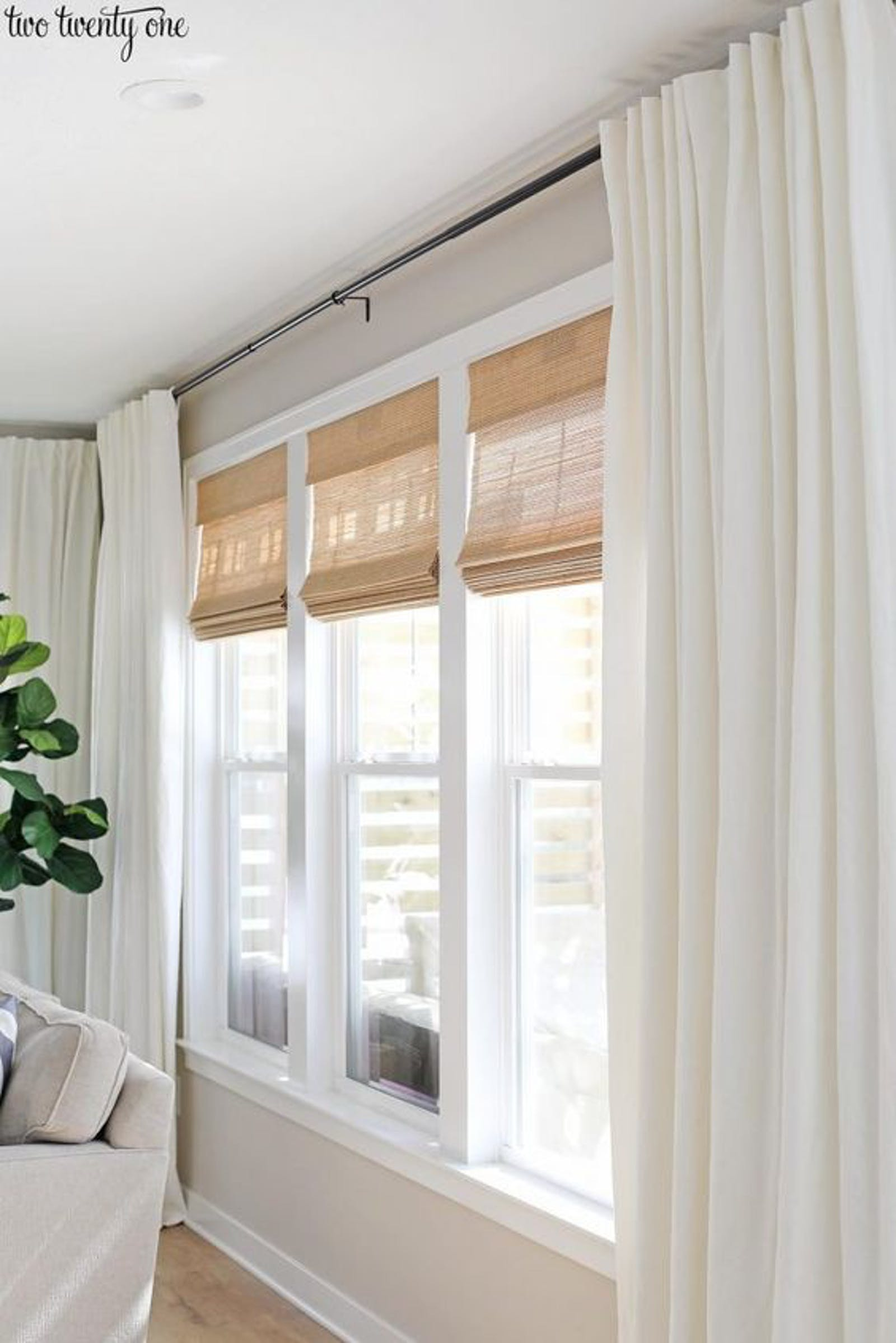 Three windows with rattan roman blinds and white floor length curtains
