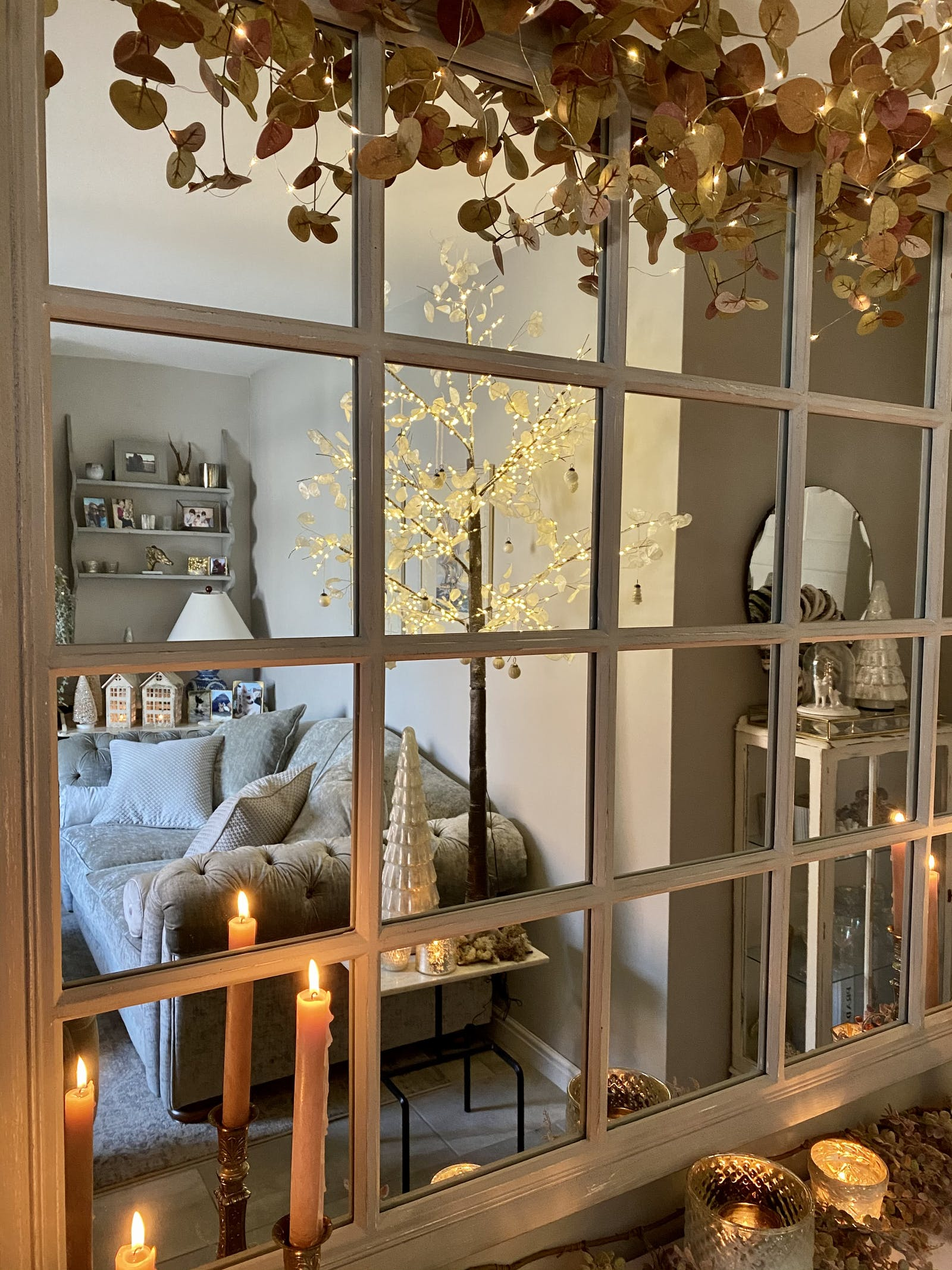 Wall mirror reflecting a Christmas decorated living room