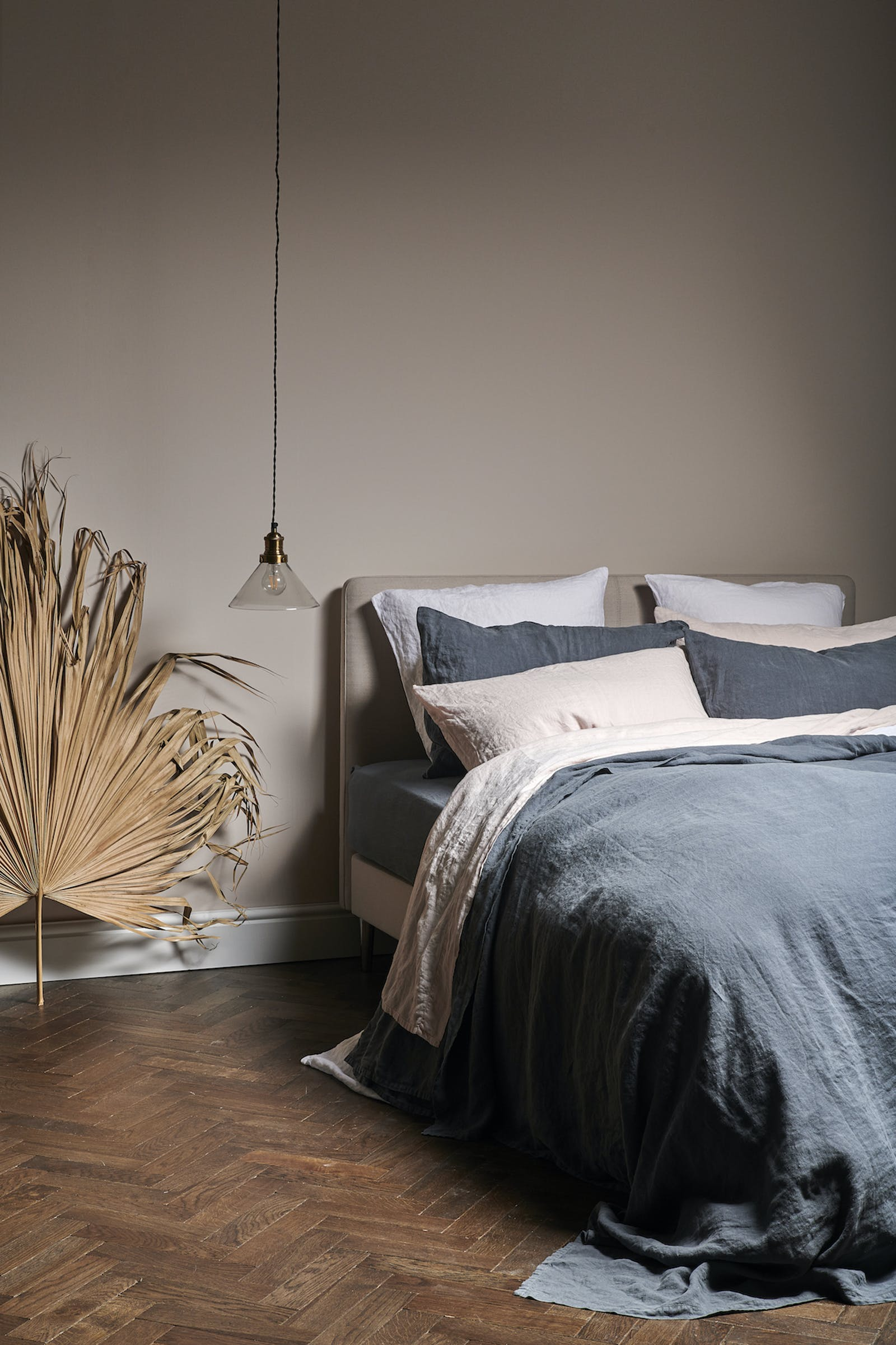 Tranquil bedroom with muted colours and layered linen bedding in beige and ink blue
