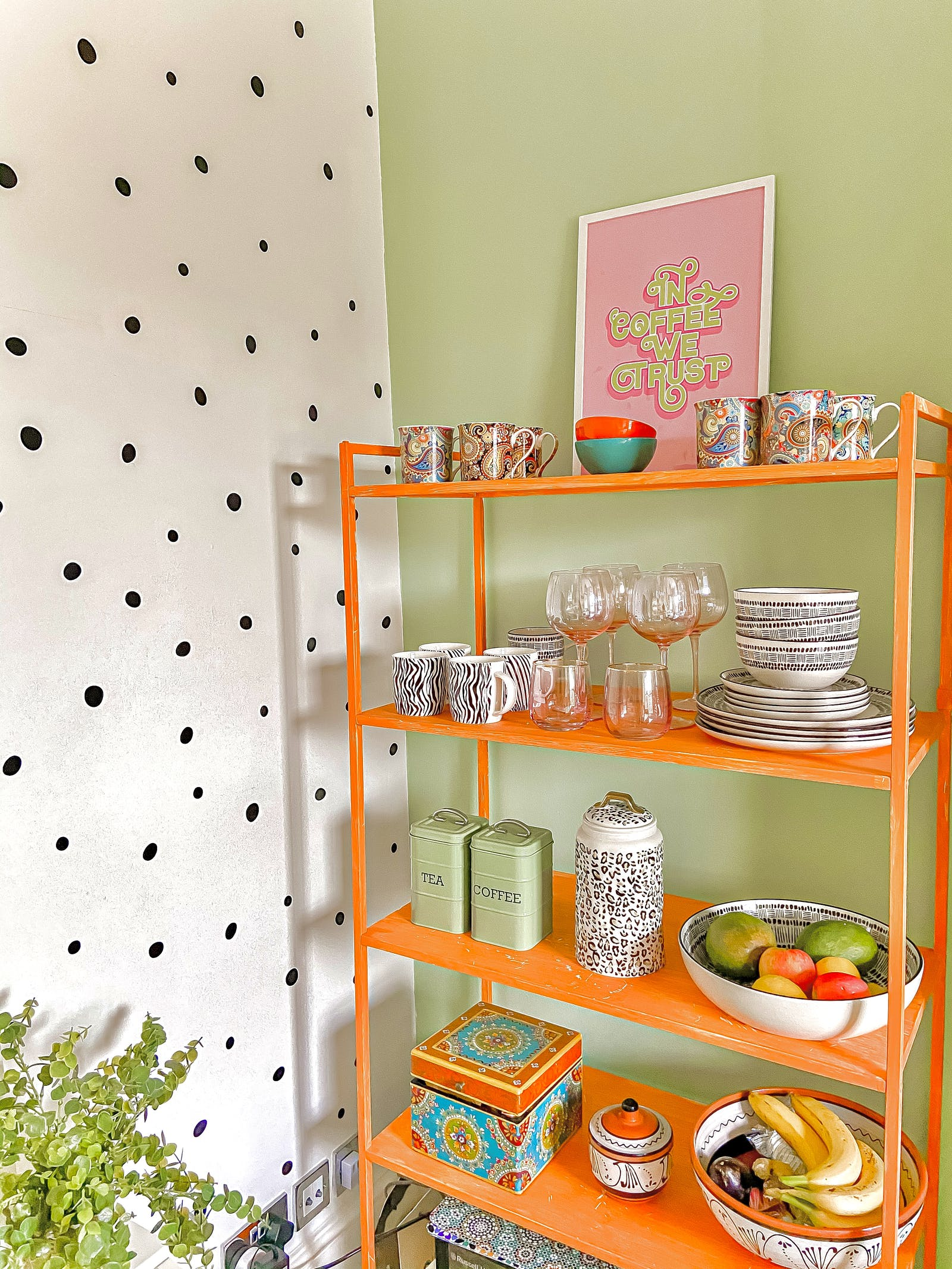 Brightly coloured kitchen with polkadot wallpaper and an orange shelf for plates and glasses