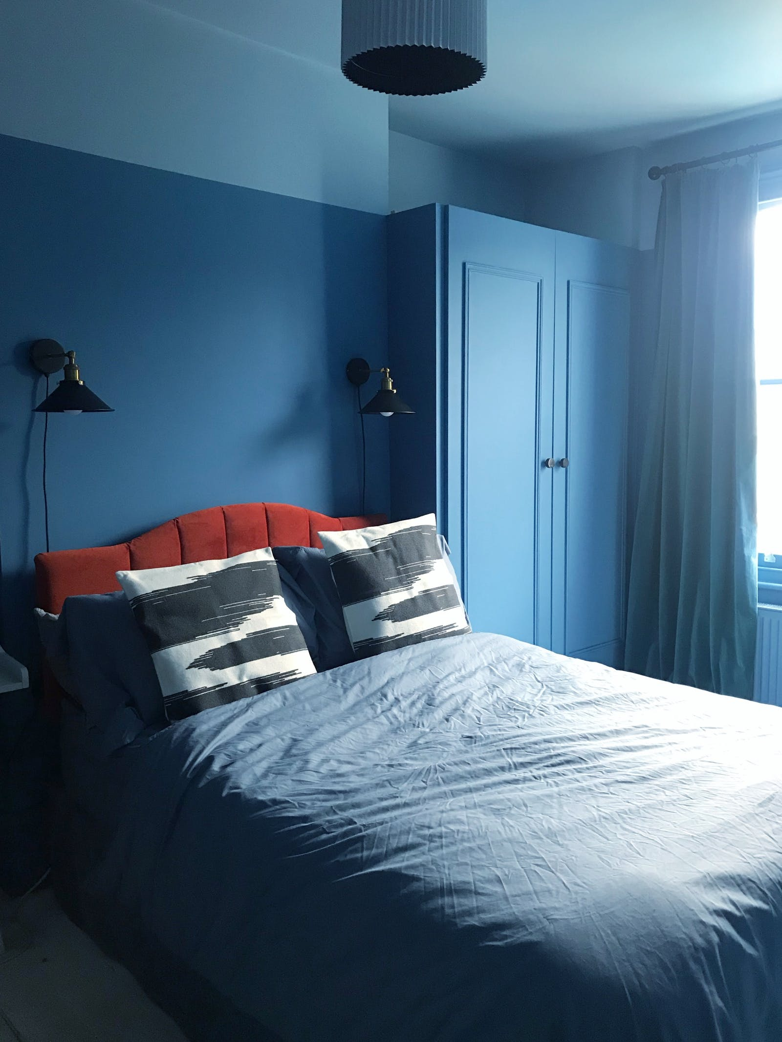Blue room painted in Lick Blue 04 and Blue 05 with red headboard