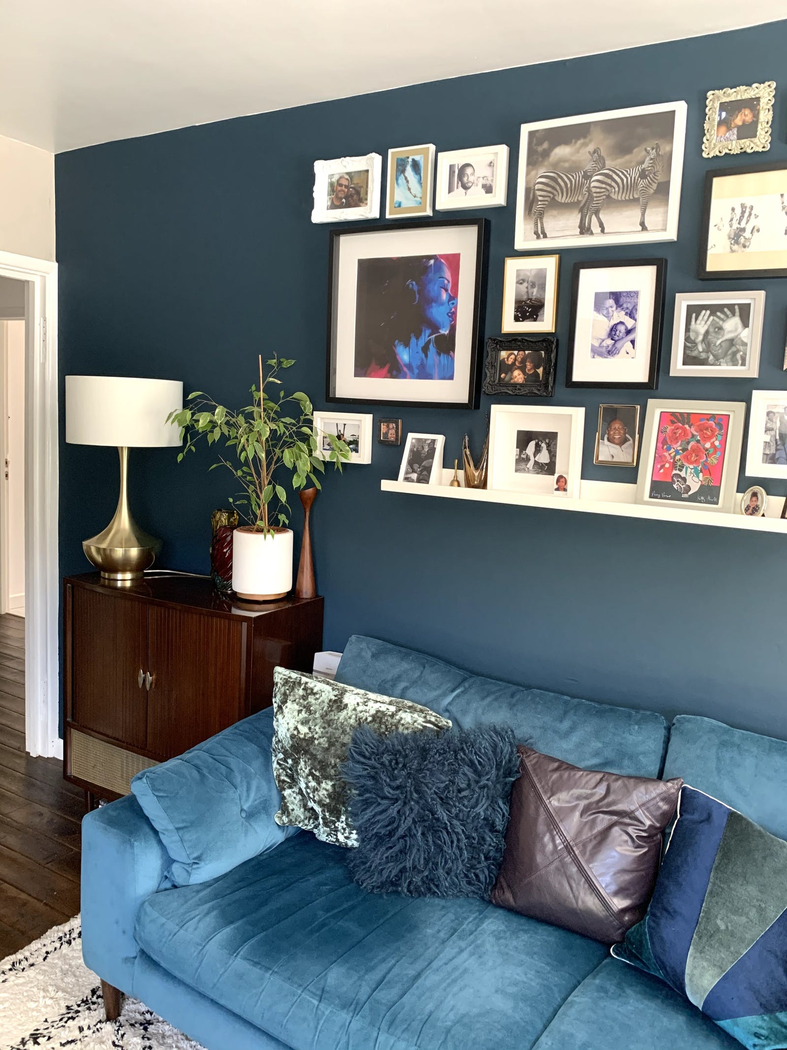 Living room painted in Lick Blue 07 with a dark blue sofa and gallery wall