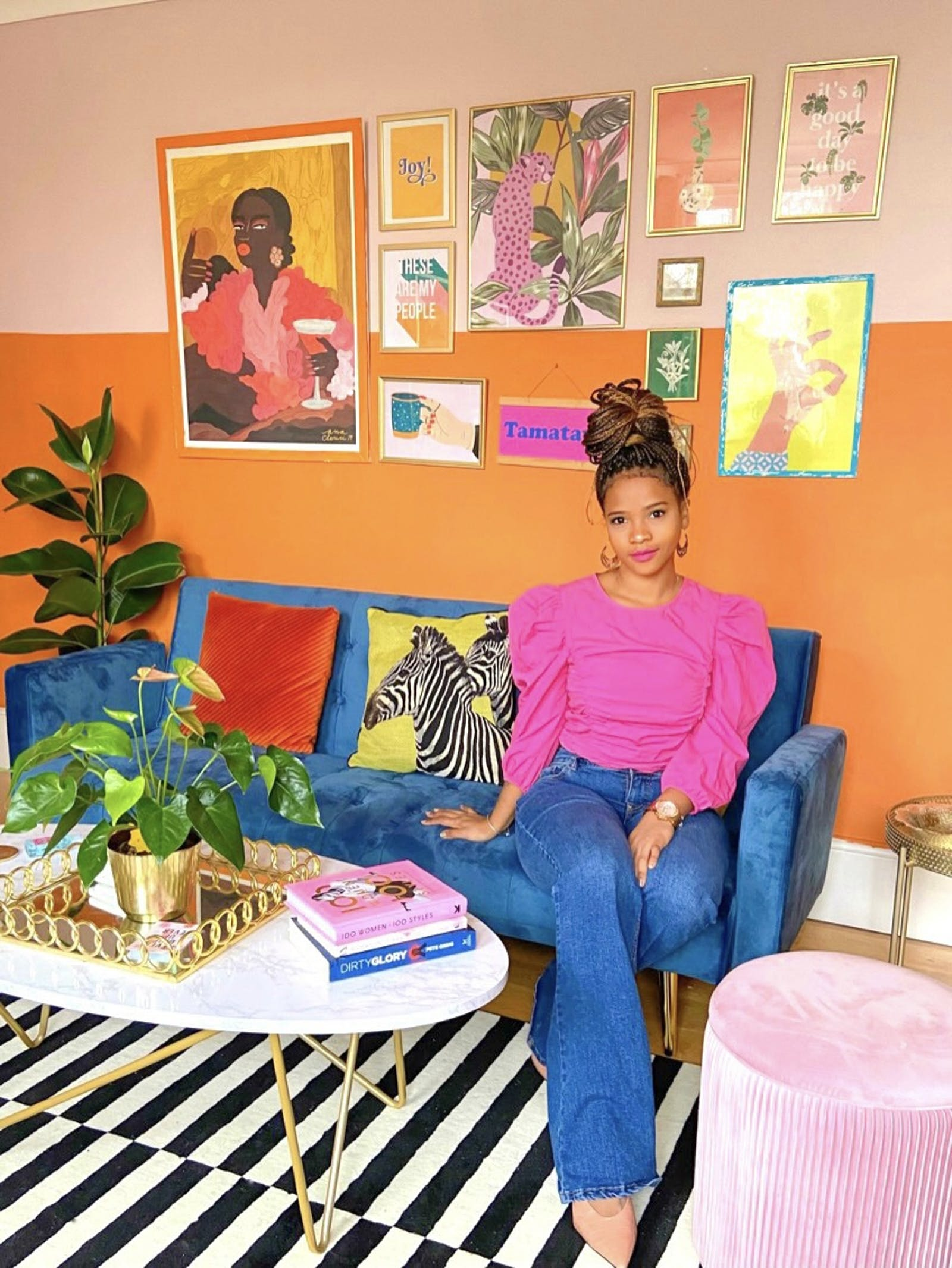 Portrait of woman sitting in brightly coloured living room with vibrant furnishings and eclectic art