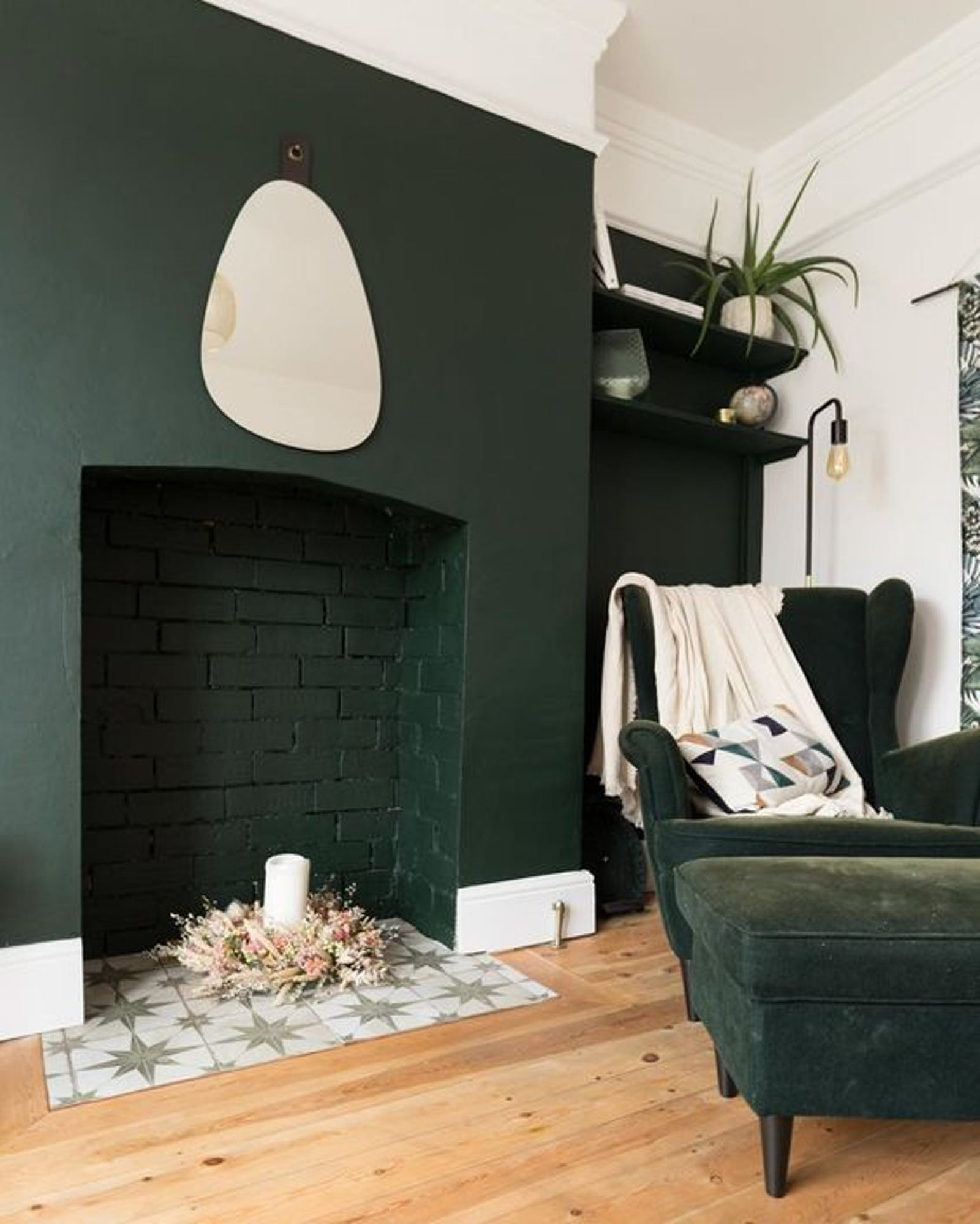 Living room painted in Lick Green 06, a dark green paired with light wooden parquet floors