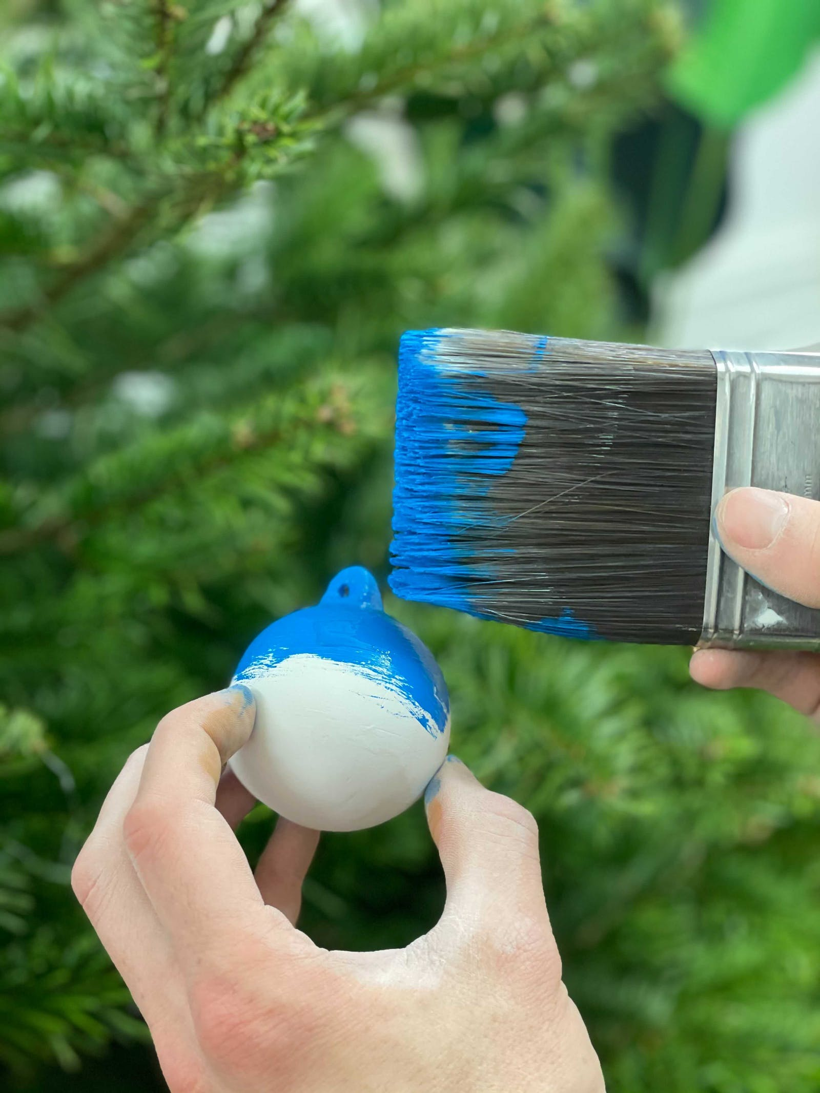 Hand holding ceramic bauble being hand painted in Lick Blue 111 in front of Christmas tree