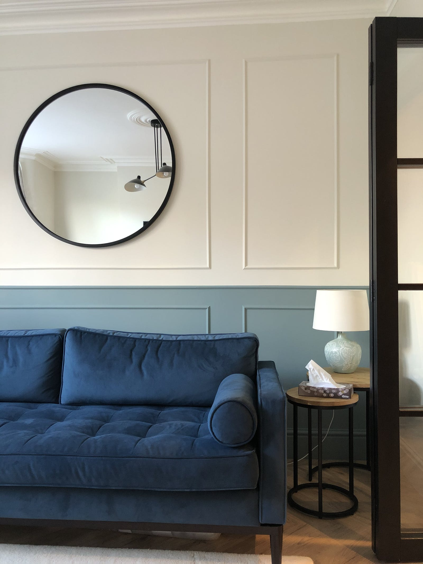 Chic living room with Teal 01 painted wall panels and dark blue sofa