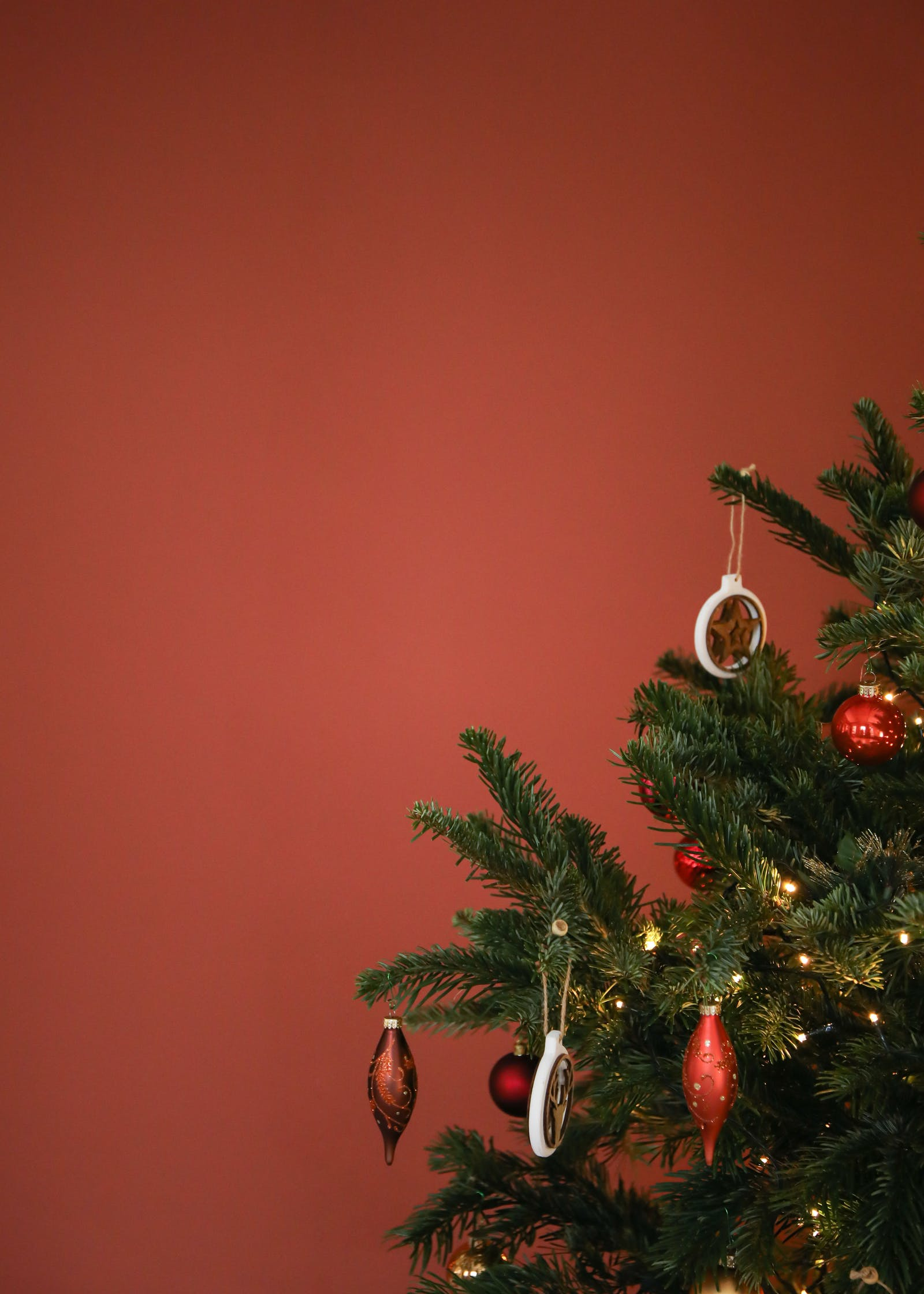 Christmas tree decorated in red baubles against Lick Red 01 wall
