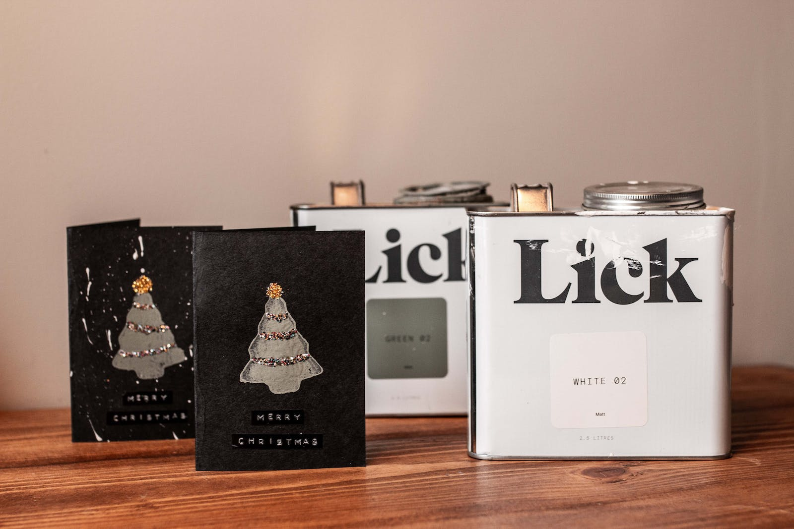 Lick tins next to handmade Christmas cards