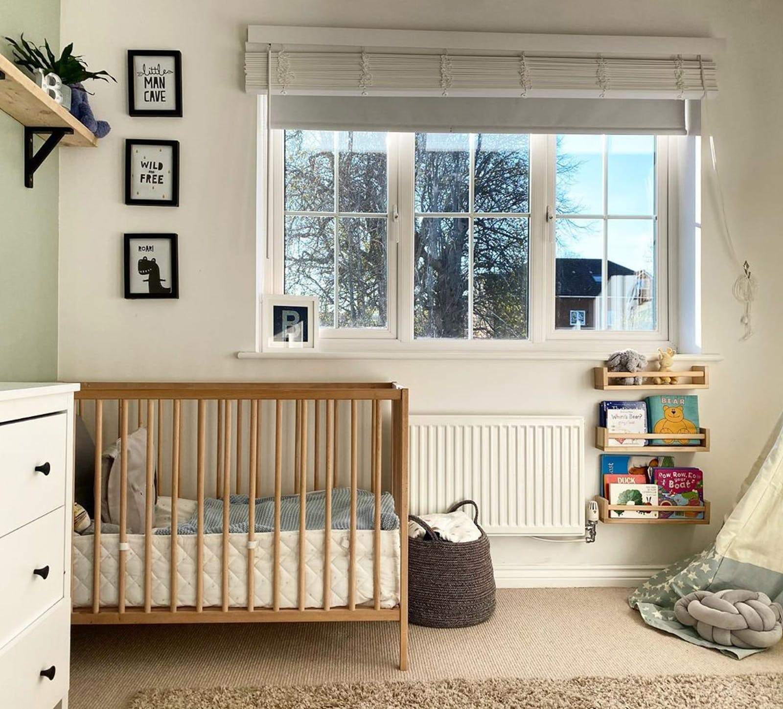 White kids bedroom with black and white artwork and big windows