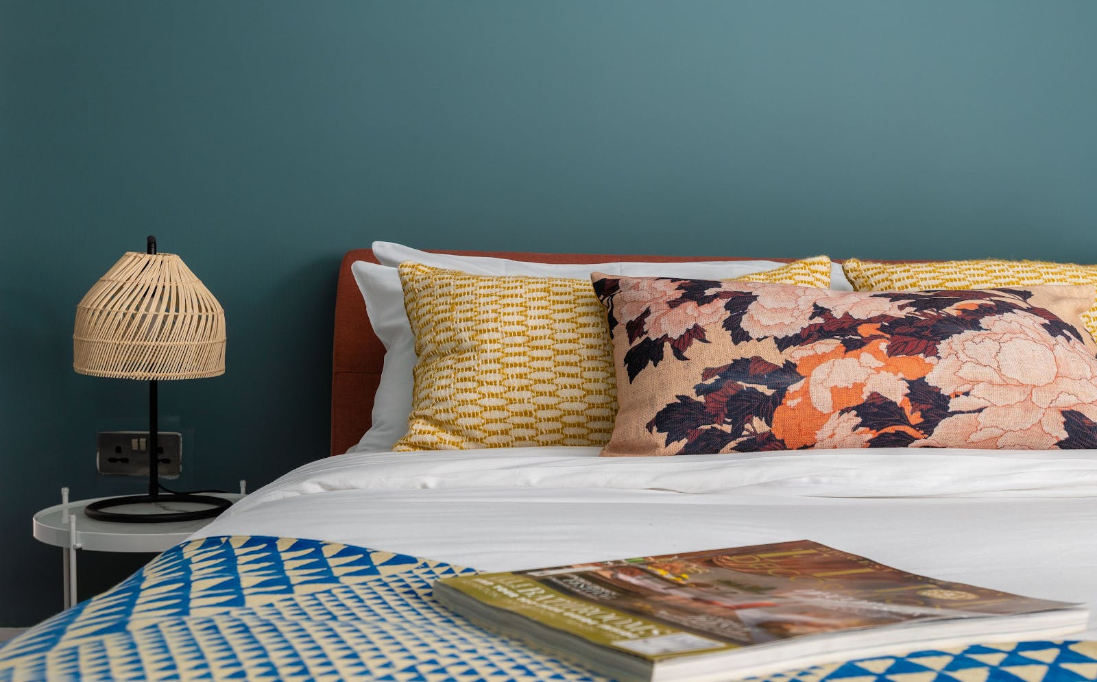 Bed with colourful floral cushions, Lick Green 04 painted walls, and a geometric throw