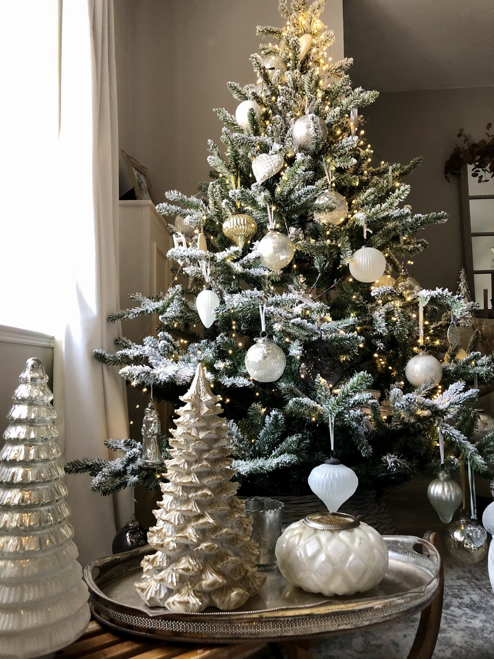 Christmas tree with snow effect and glass baubles in white, gold and ivory