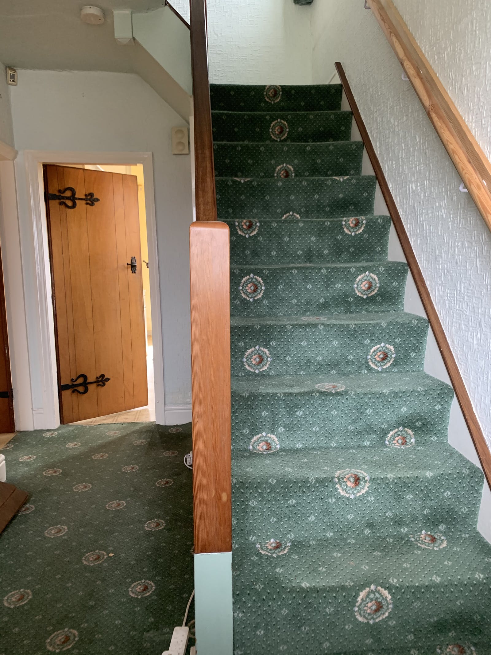 Image of hallway with dated green carpet running up stairs