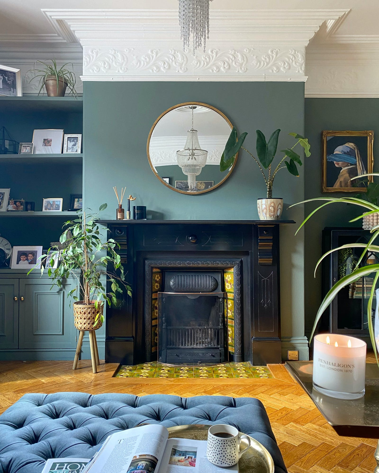 Living room painted in sage green with natural wood floor, navy blue sofa and plants