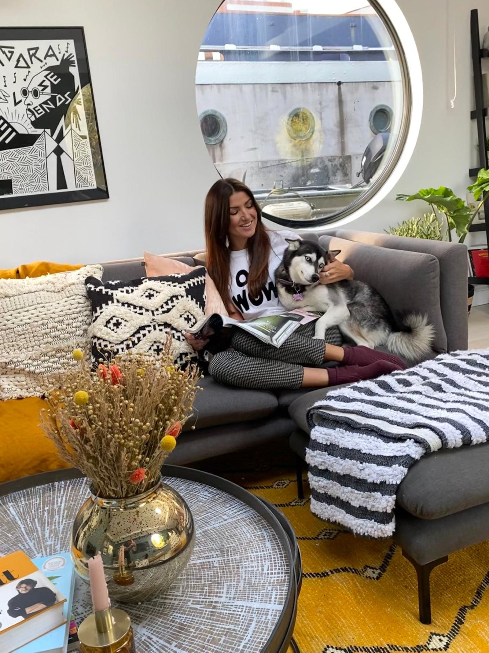 Christina Miles from @thisonefloats with her dog sitting in an eclectic living room